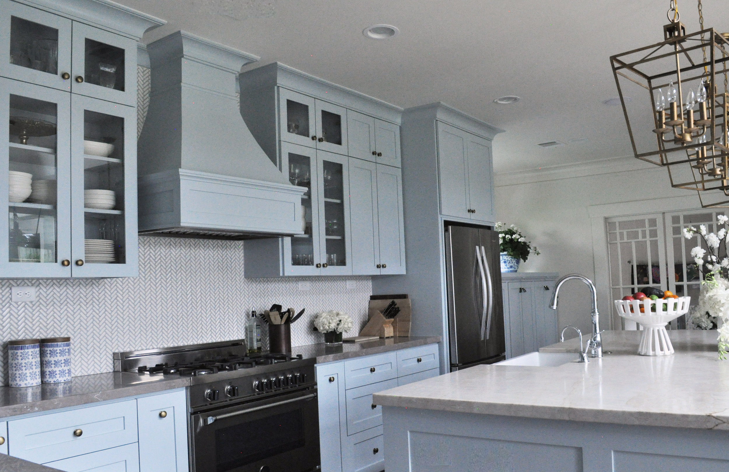 Traditional bungalow kitchen, with blue cabinets, with large marble island designed by Jamie House Design