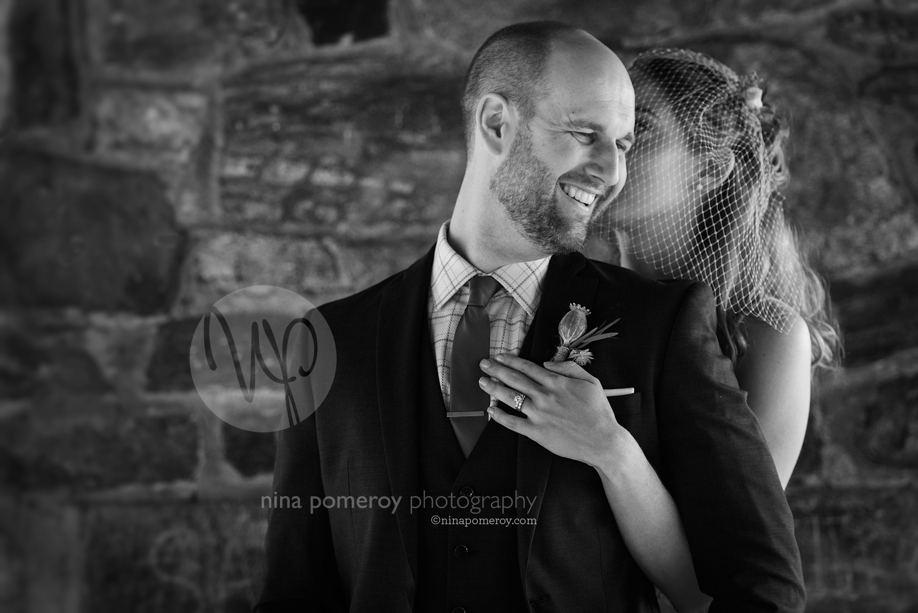 B&W photo of Bride kissing and hugging a smiling groom at a small outdoor garden vineyard wedding by livermore photographer nina pomeroy