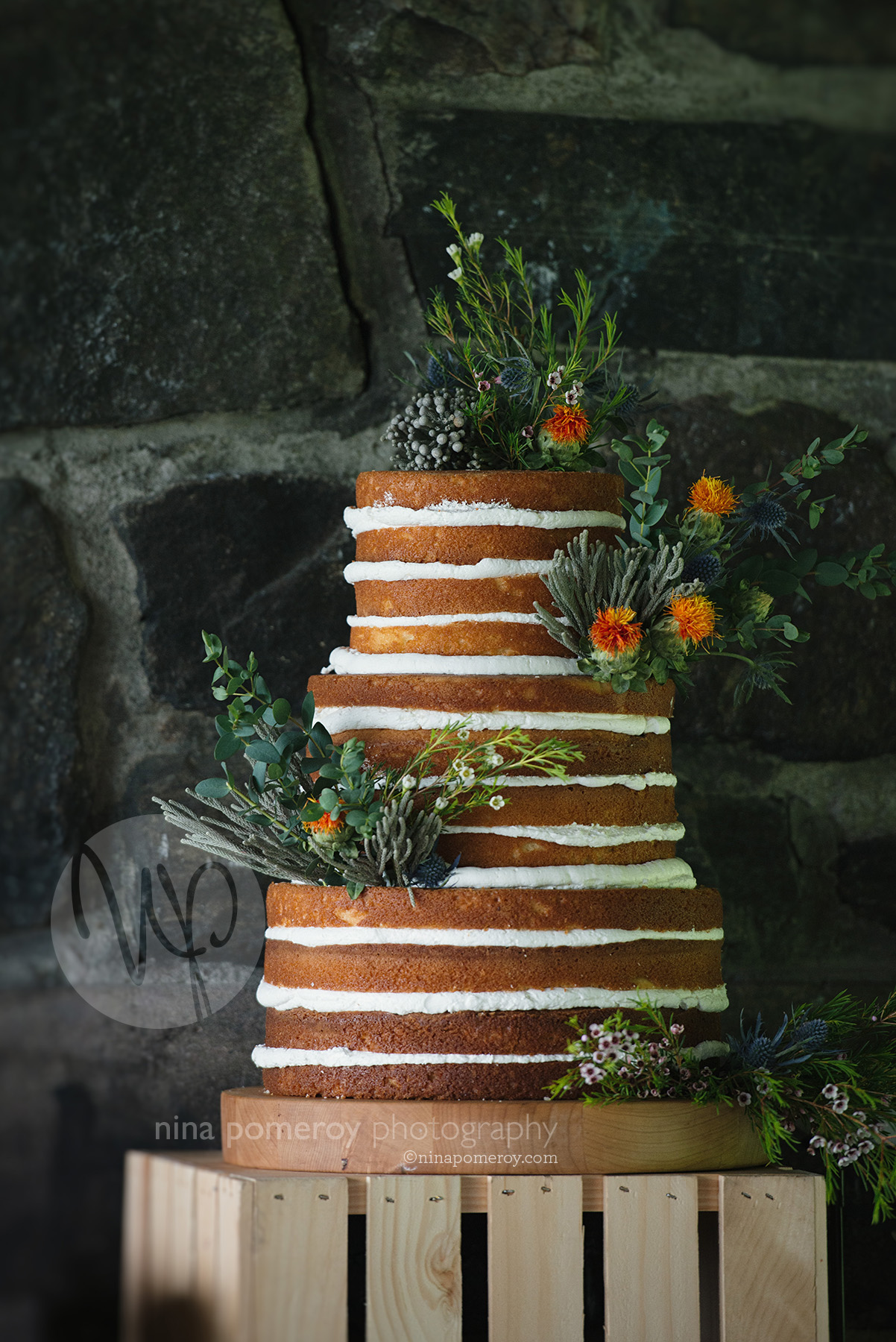 naked un-iced wedding cake embellished with flowers for this beautiful napa garden vineyard wedding taken by photographer nina pomeroy
