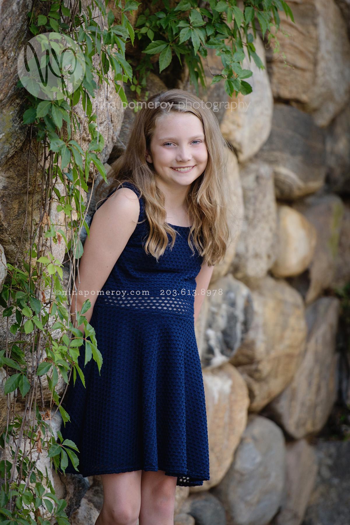 Tween teen girl portrait by rock wall and ivy wearing a blue dress taken by bay area photographer Nina Pomeroy.