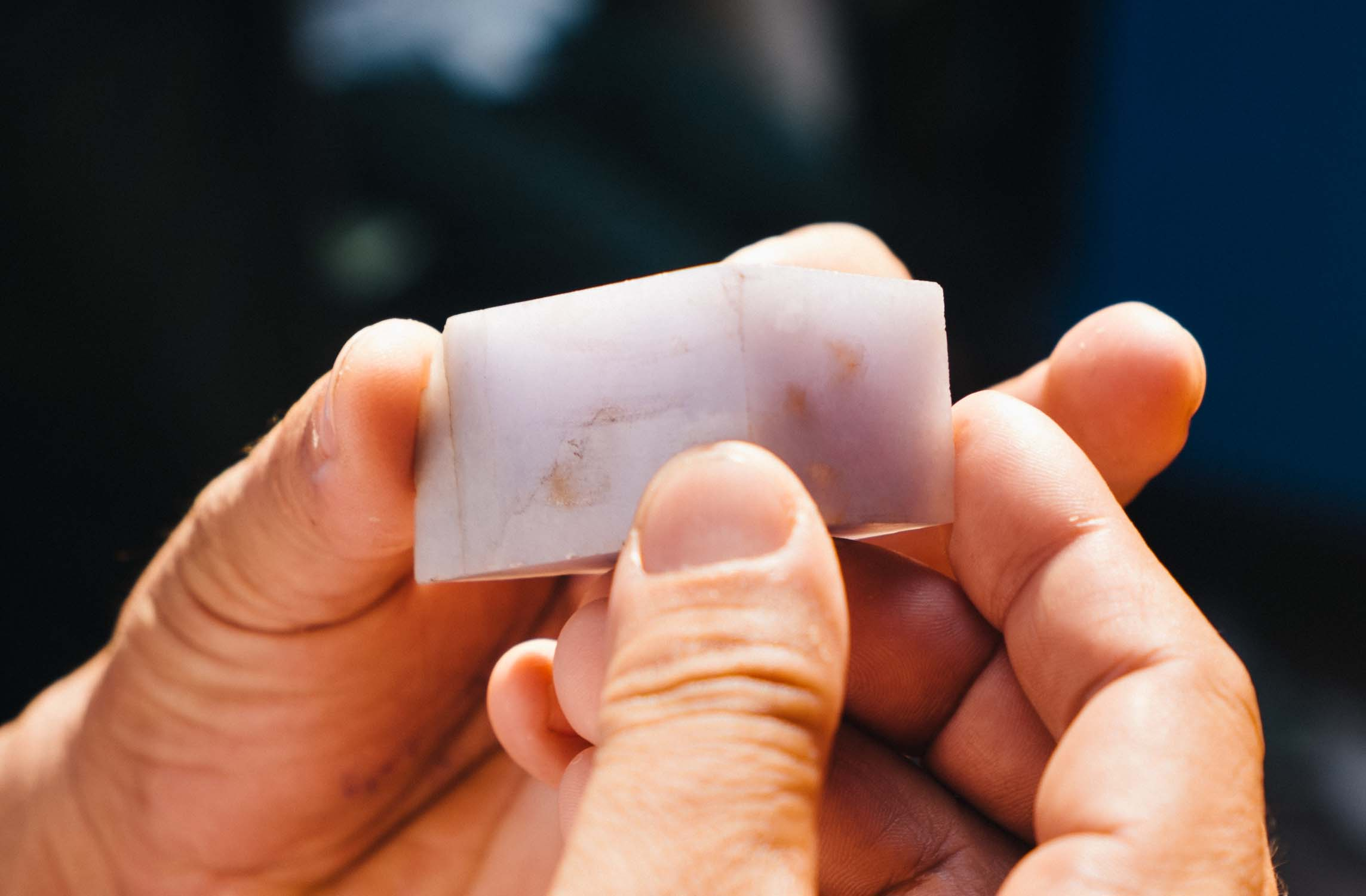 A block  of lavender jade being evaluated.