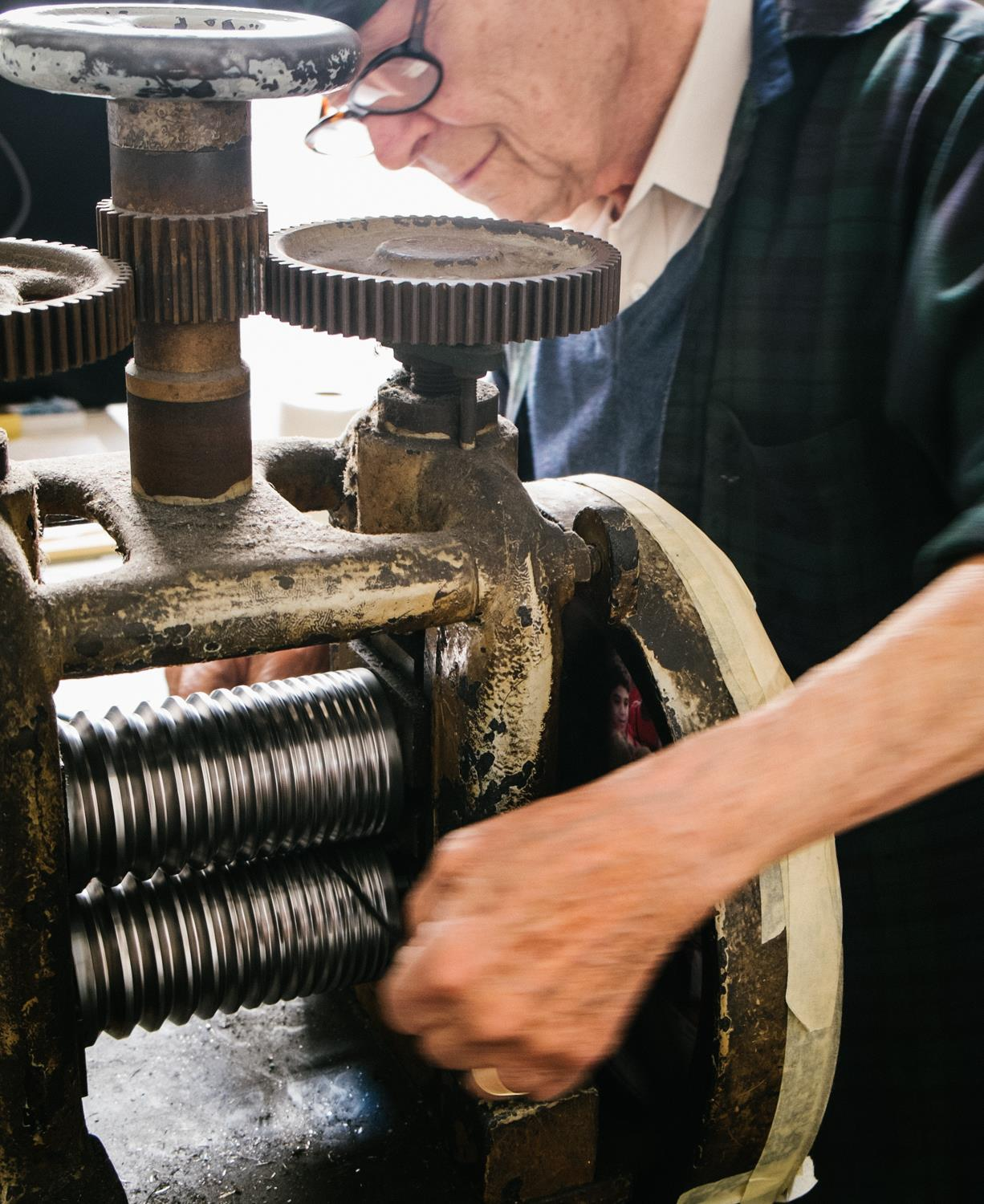 The platinum disk is passed through a metal roller multiple time in order to form wire.
