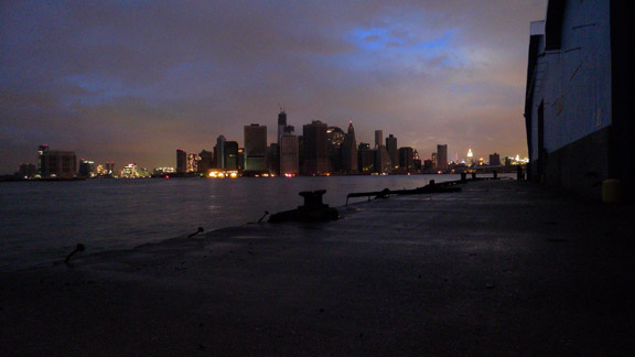 Lower Manhattan without power except at  Staten Island Ferry Terminal.     Jersey to the left, midtown to the right.  Upsticking bolts show where head logs were ripped off the pier by Sandy.