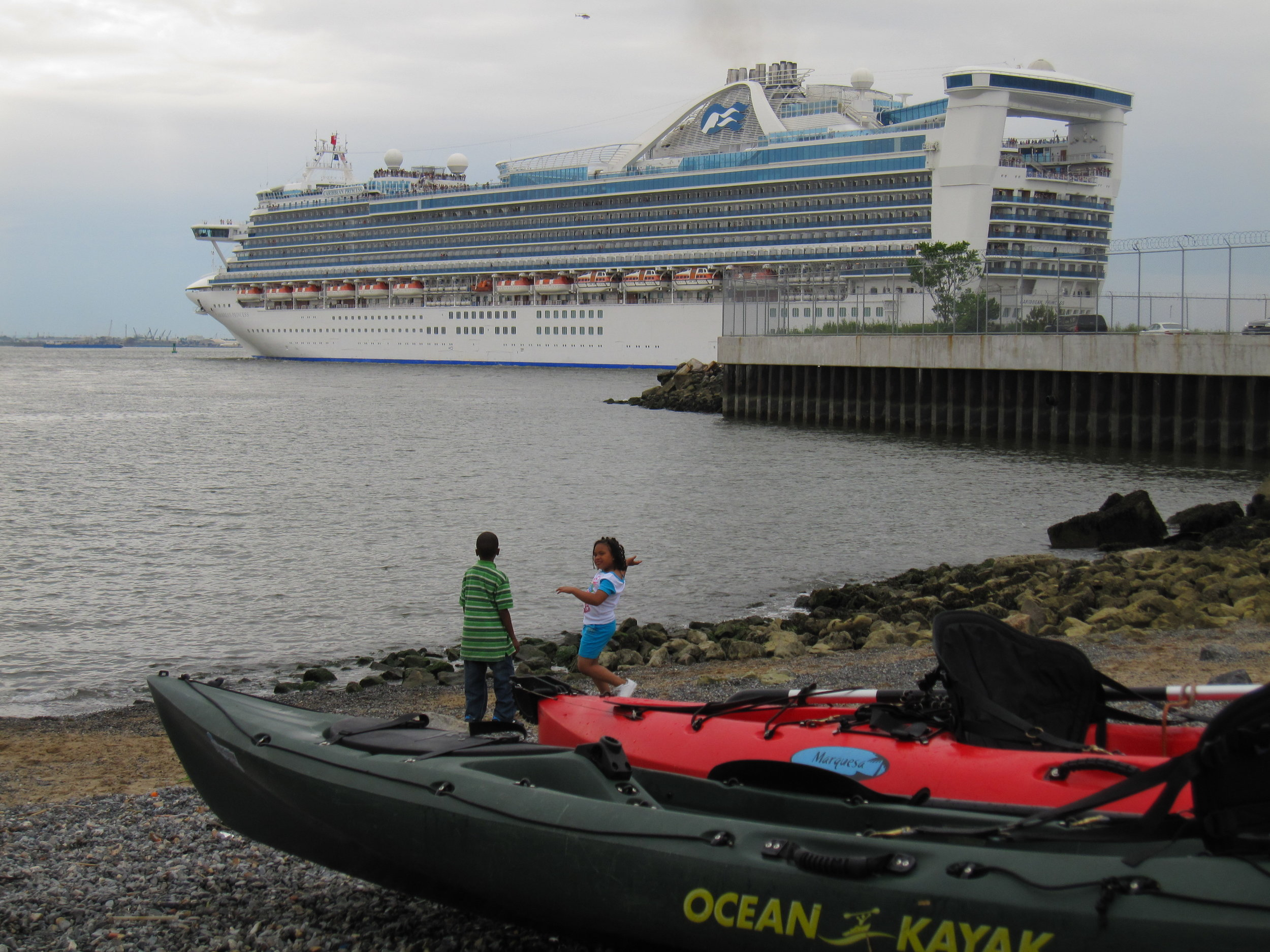 A cruise ship leaves the Brooklyn Cruise Terminal in Red Hook, close to the Valentino Park beach where kayaks come and go, an example of the huge difference in scale of boats in close proximity on NYC waterways.