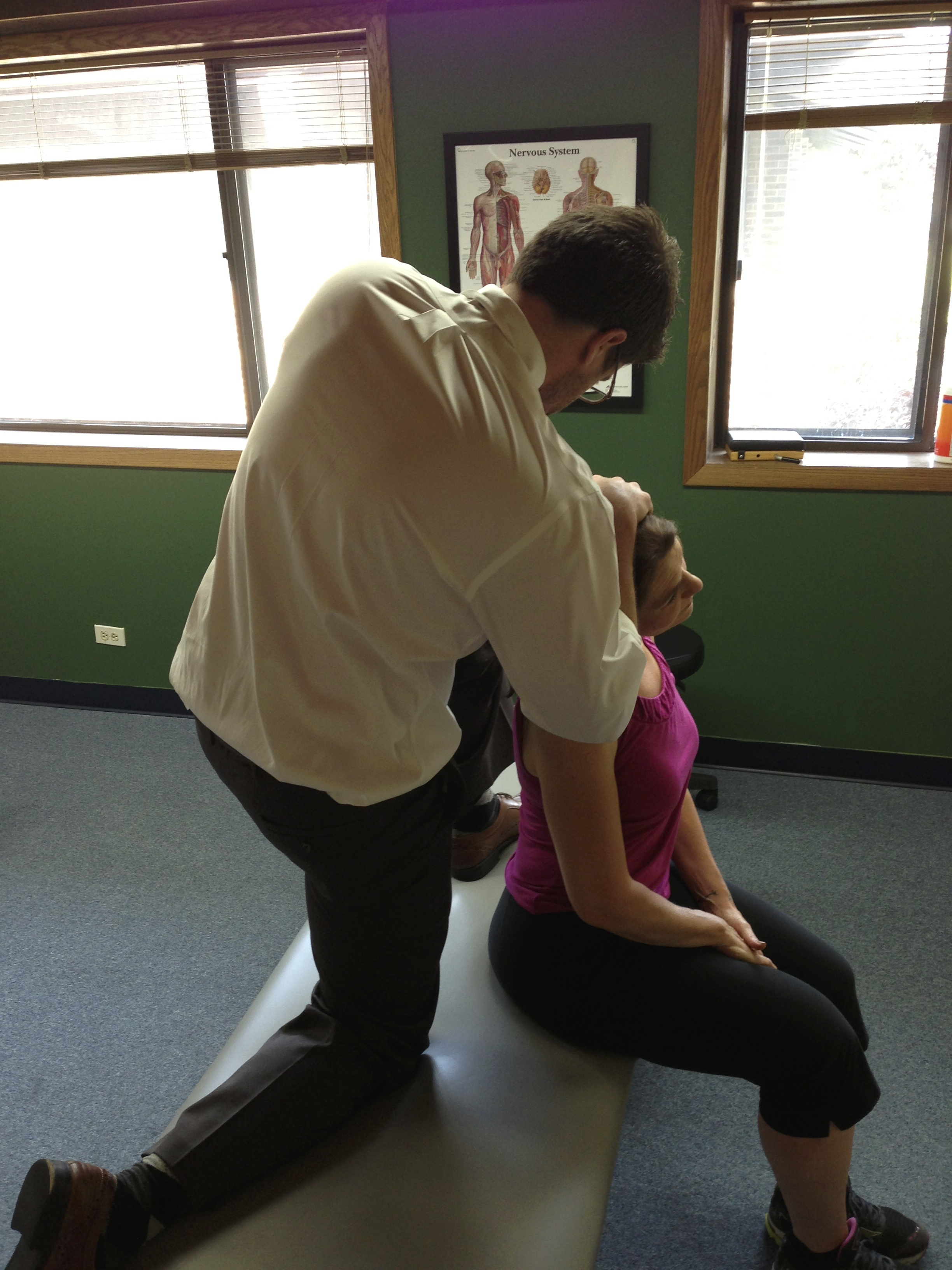 Dr. Chris Examines someone experiencing cervicogenic headaches at our Victory Rehab office in Naperville.