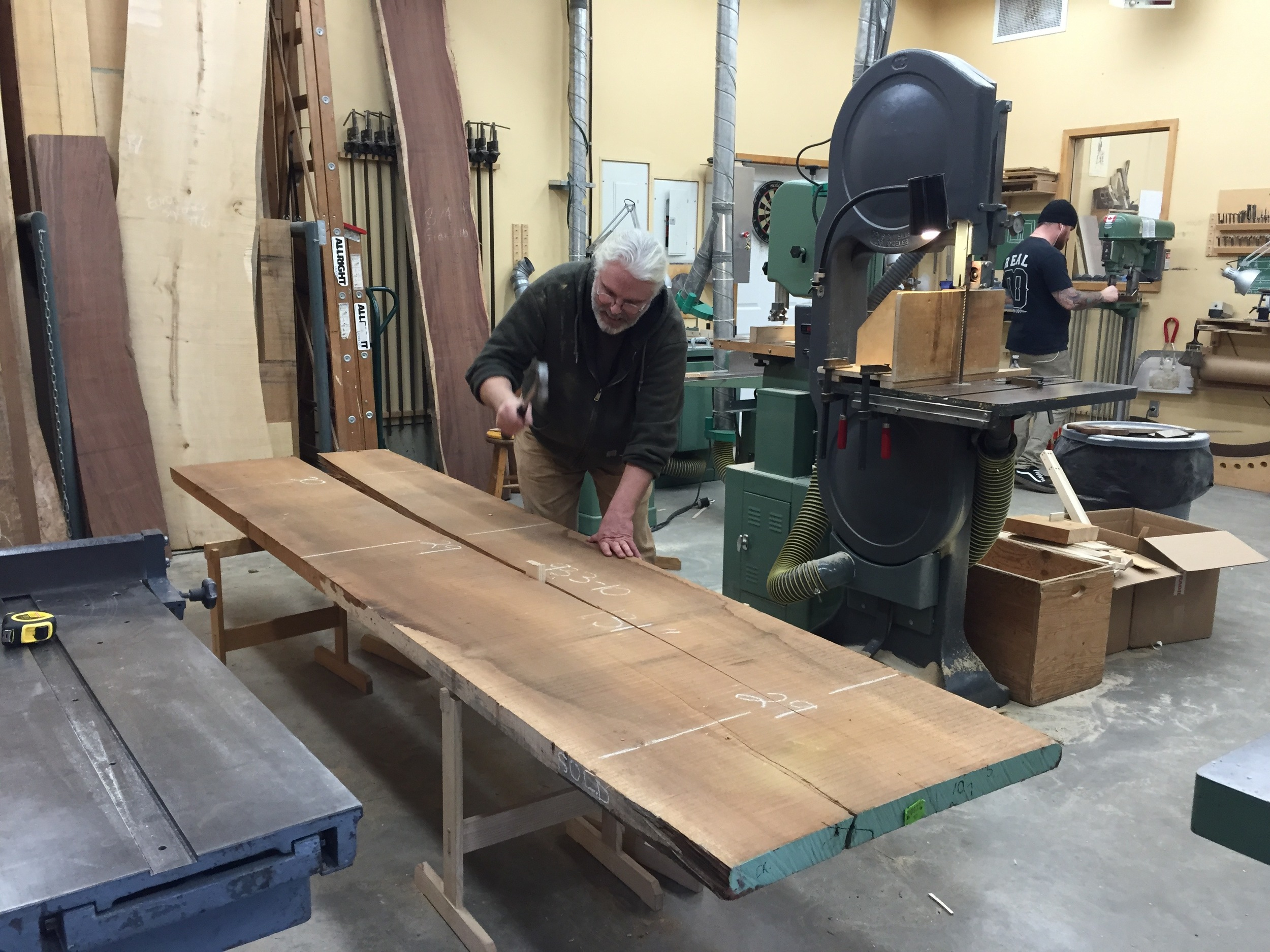 Robert splits a plank of Doussie along an existing crack, for easier storage