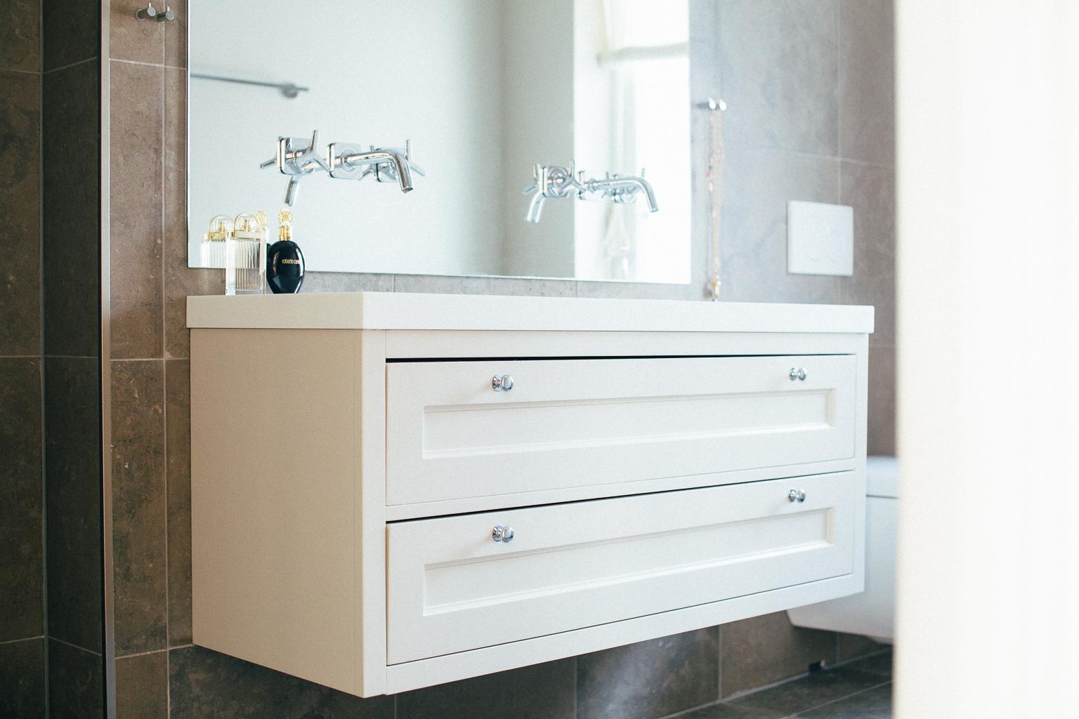 Baderomsseksjonen har gode skuffeløsninger og en lang vask støpt i hvit Corian.