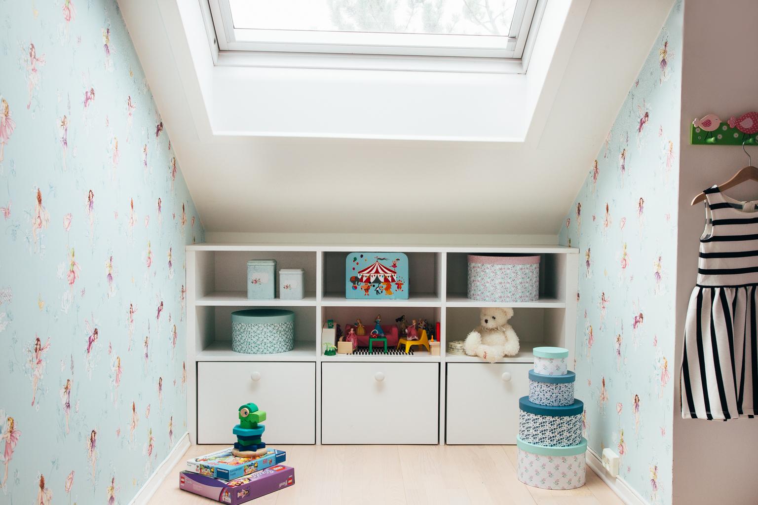 Hyllene på barnerommene er tilpasset skråtaket. Skuffene kan dras ut og fungerer som oppbevaringsbokser.