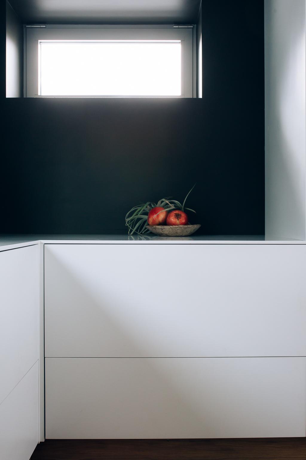 De gode lysforholdene fremhever  de rene flatene på kjøkkenet og tillater en mørk farge på veggene .
