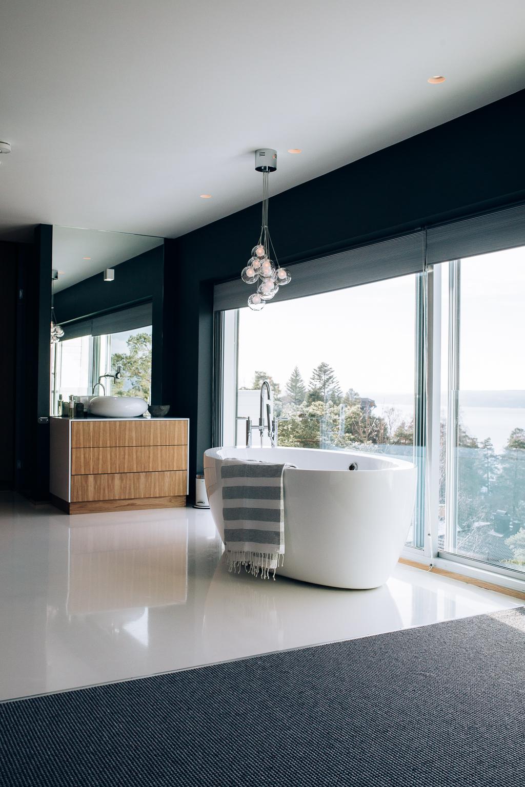Soverommet og badet har samme farge- og materialvalg som resten av villaen.Tøft valg med åpen baderomsløsning og ikke minst en fantastisk utsikt.