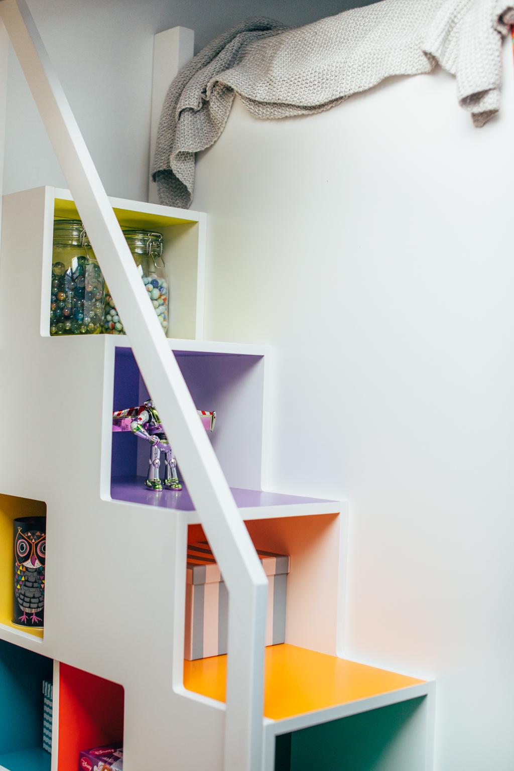Trappen opp til sengen har masse plass til oppbevaring av leker. Dessuten er den malt i morsomme farger.
