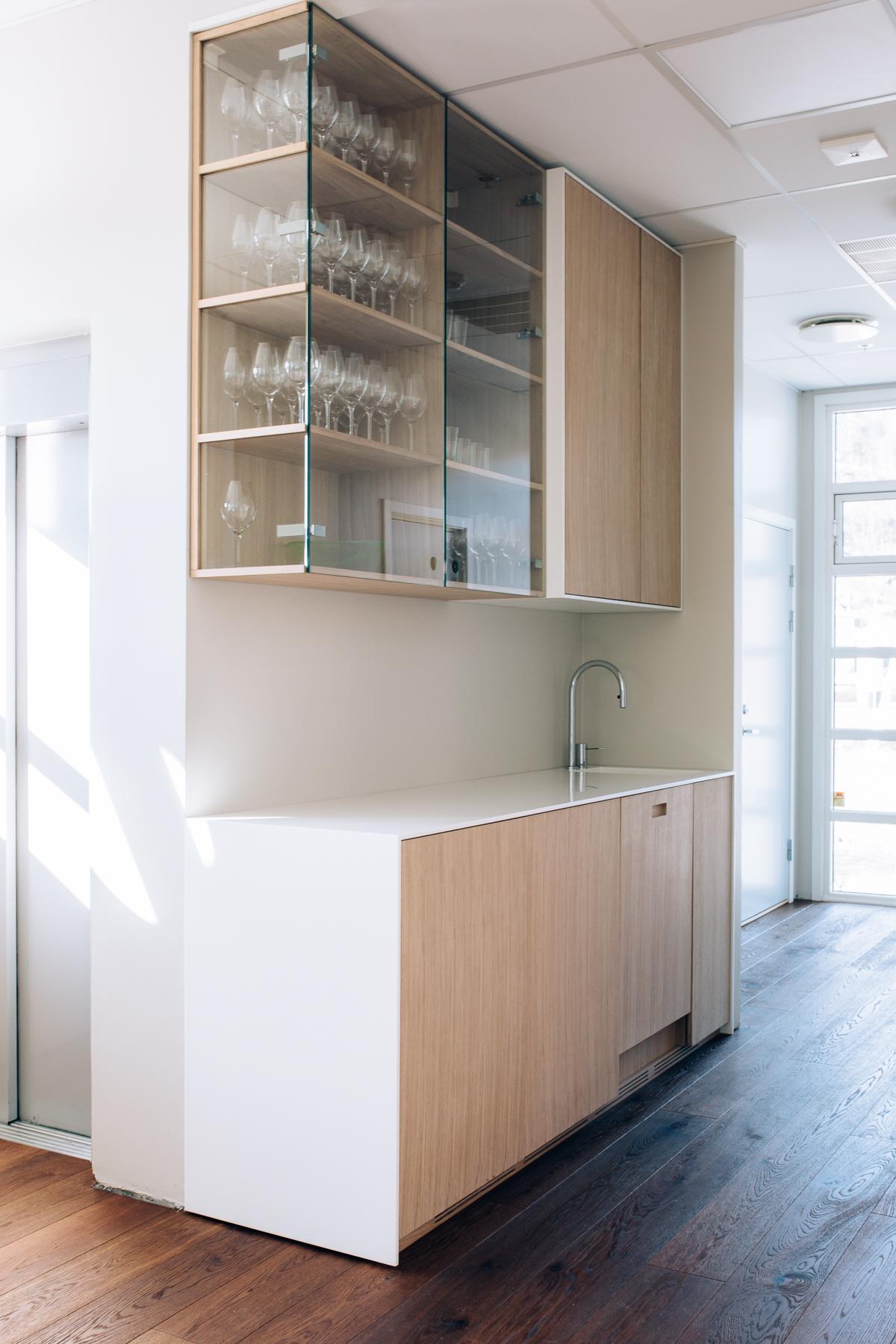 Kontoret har et eget kjøkken med overskap delvis i glass. Som resten av kontoret, får kjøkkenet et rent og luftig uttrykk.