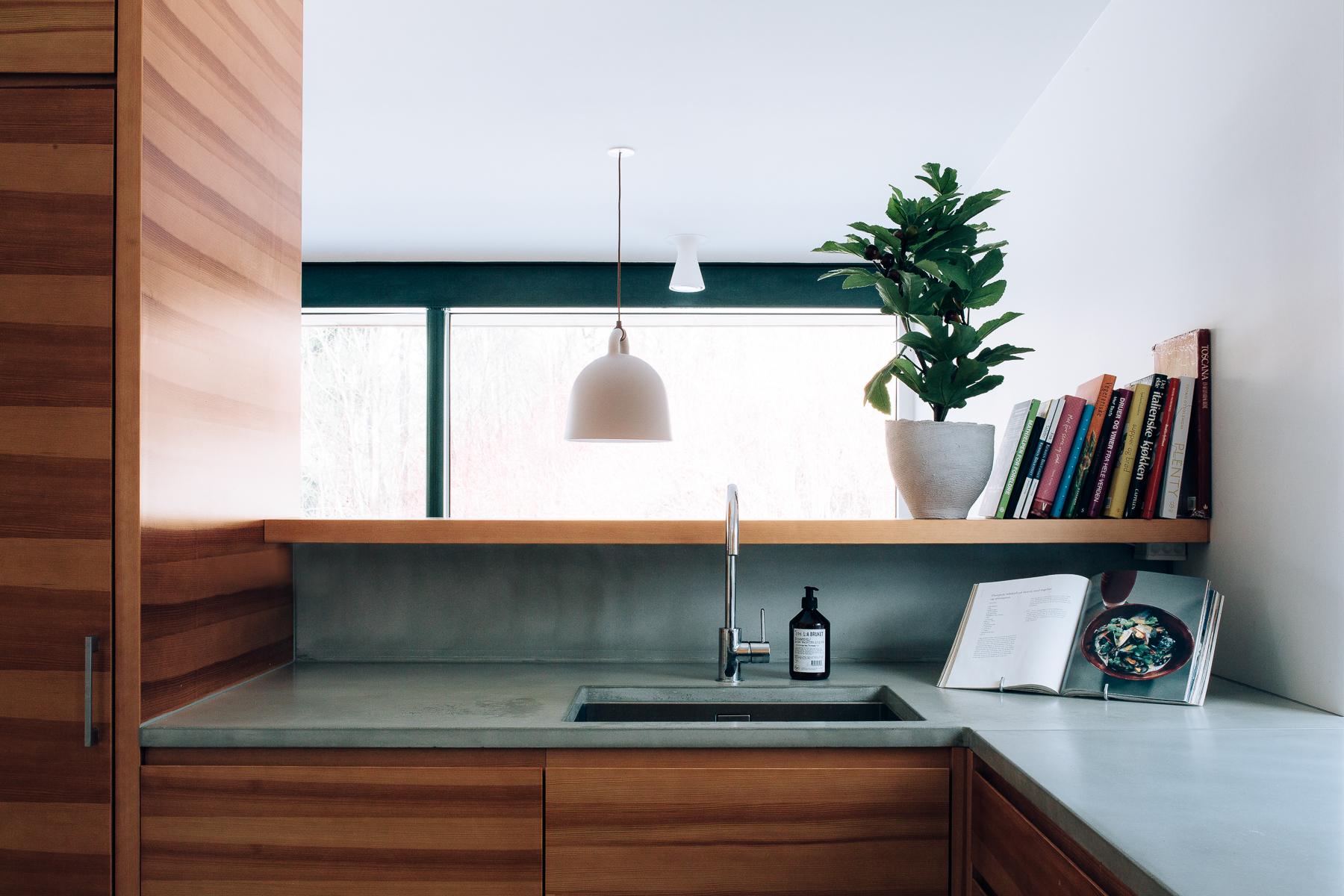 Kompakt kjøkken med   opphøyet disk.  Kjøkkenet er  i pigmentert furu og har et spennende materialuttrykk. Benkeplaten i betong legger en siste touch på prosjektet.