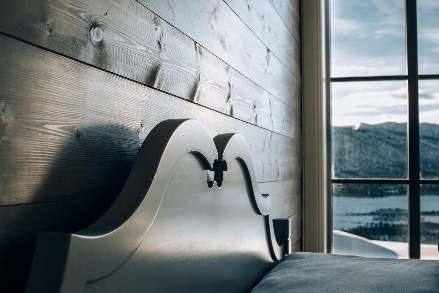 Sengen på masterbedroom har tradisjonelle utskjæringer og passer perfekt til hyttas varme stil.