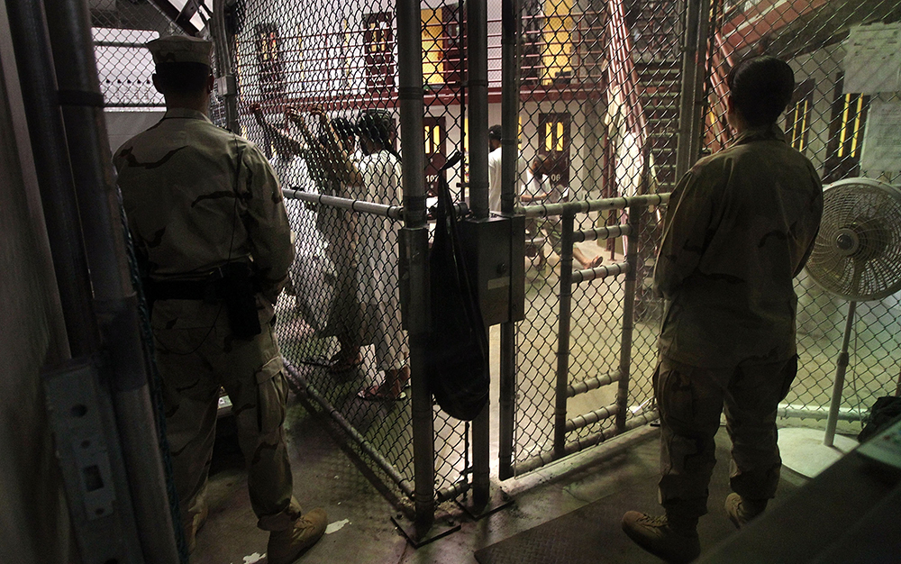 U.S. military guards watch detainees in a cell block at Camp 6 in the Guantanamo Bay detention center. (John Moore/Getty Images)