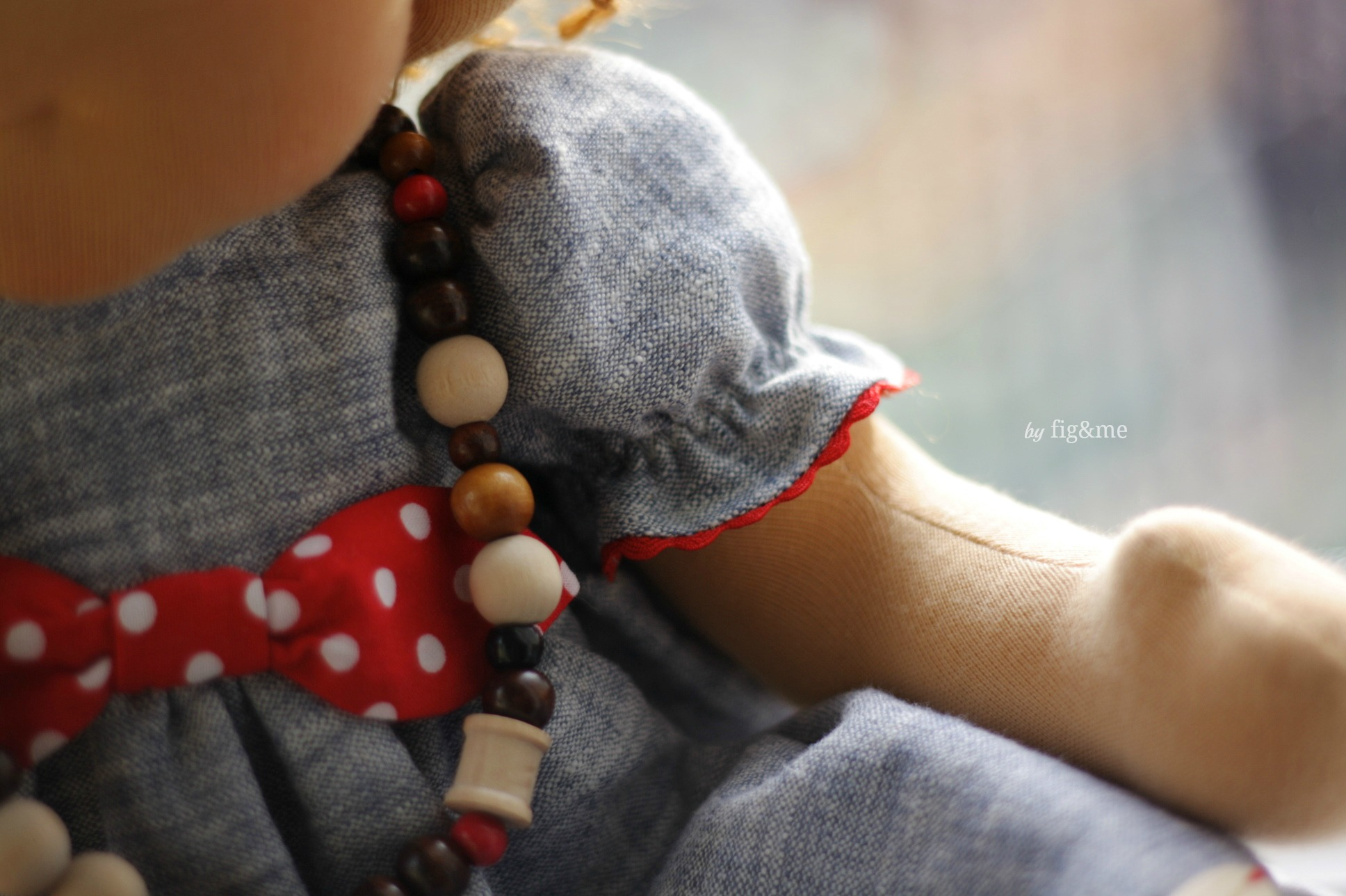 Little puff sleeve, with red ric rac, wooden bead necklace and polka dot bow.