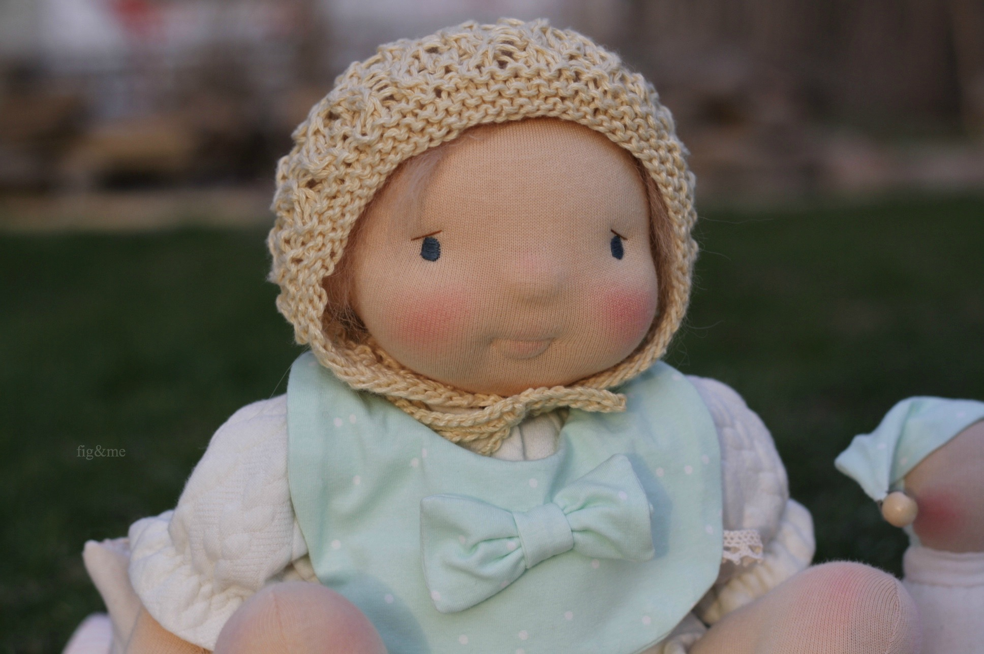 Robina wears her pretty lace bonnet and bow bib, by Fig and me.