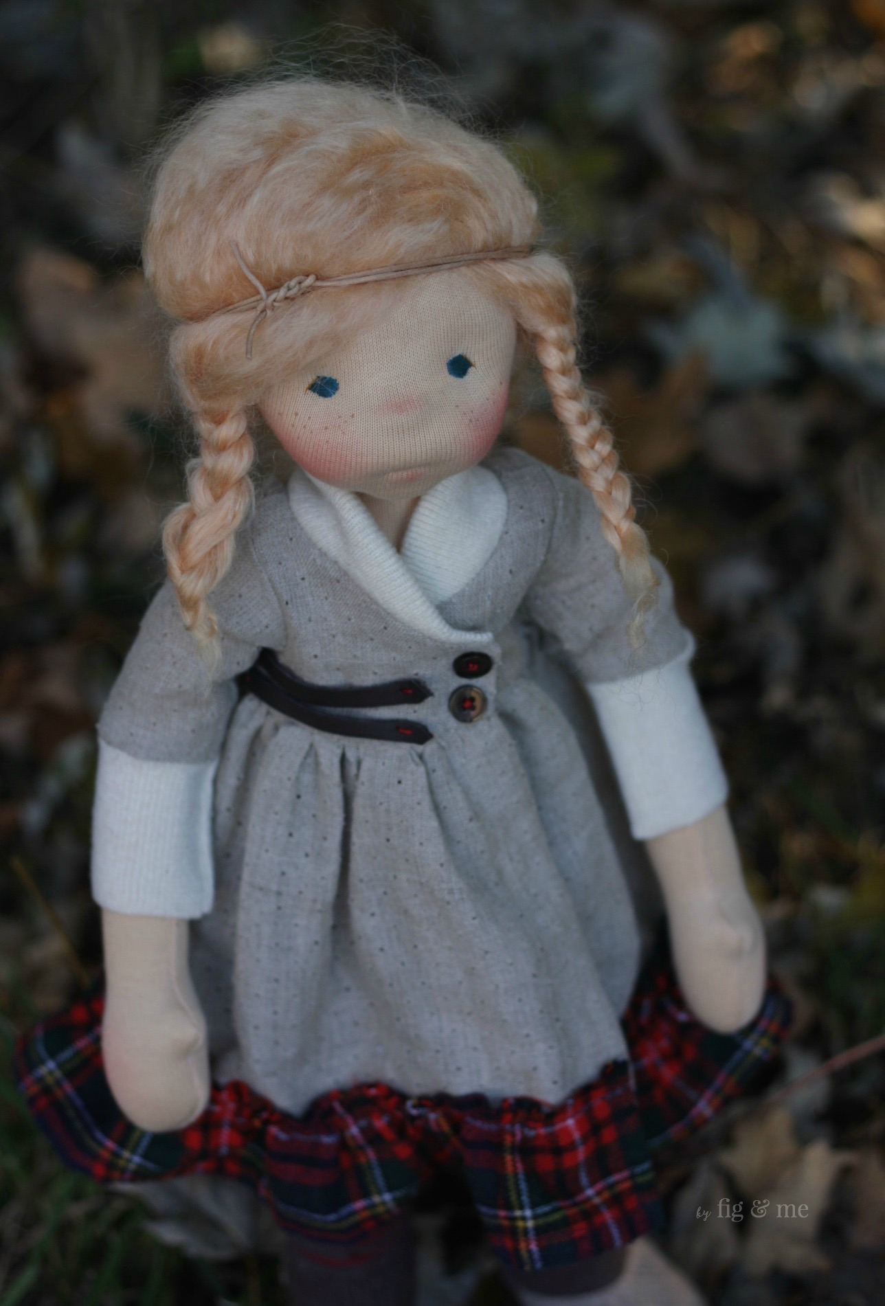 Iona, a natural fiber art doll, wearing her linen and tartan dress with leather details and shawl collar. By Fig and Me.