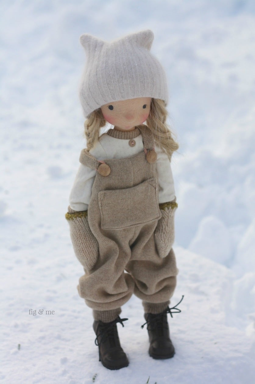 Nova wearing her organic cotton top, her wool mitten, merino overalls, boots and angora bonnet. A natural doll by Fig and Me.
