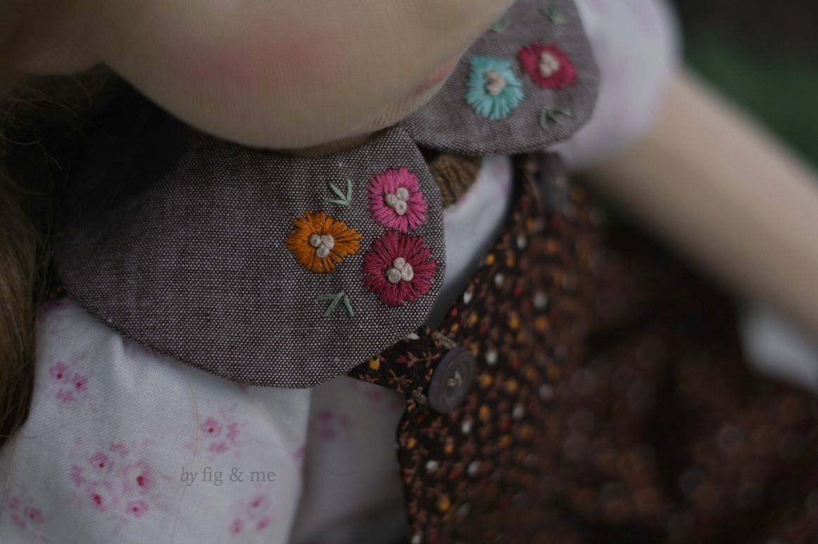 Hester wears a little circular collar with embroidered flowers, by Fig and Me.