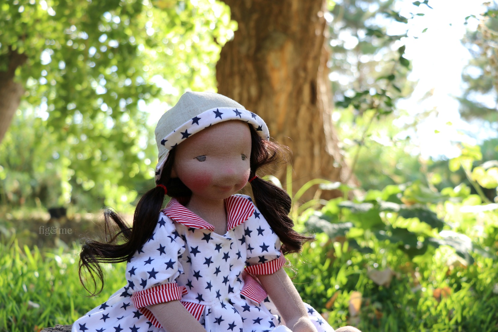Eileen sitting in the garden. A contemporary fiber art doll by Fig and Me.