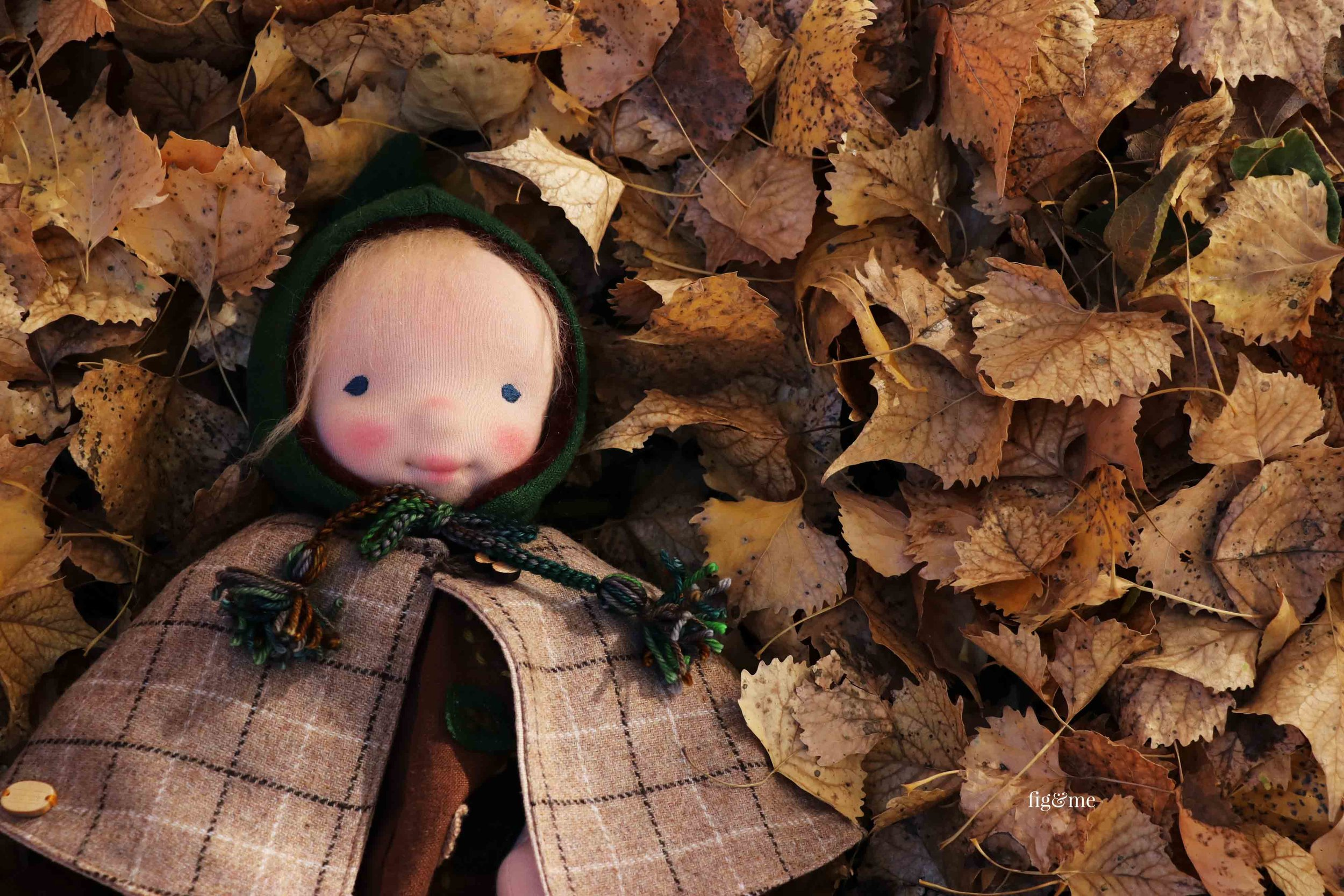 Aelfreda in a nest of leaves, a natural fiber art doll by Fig and Me.