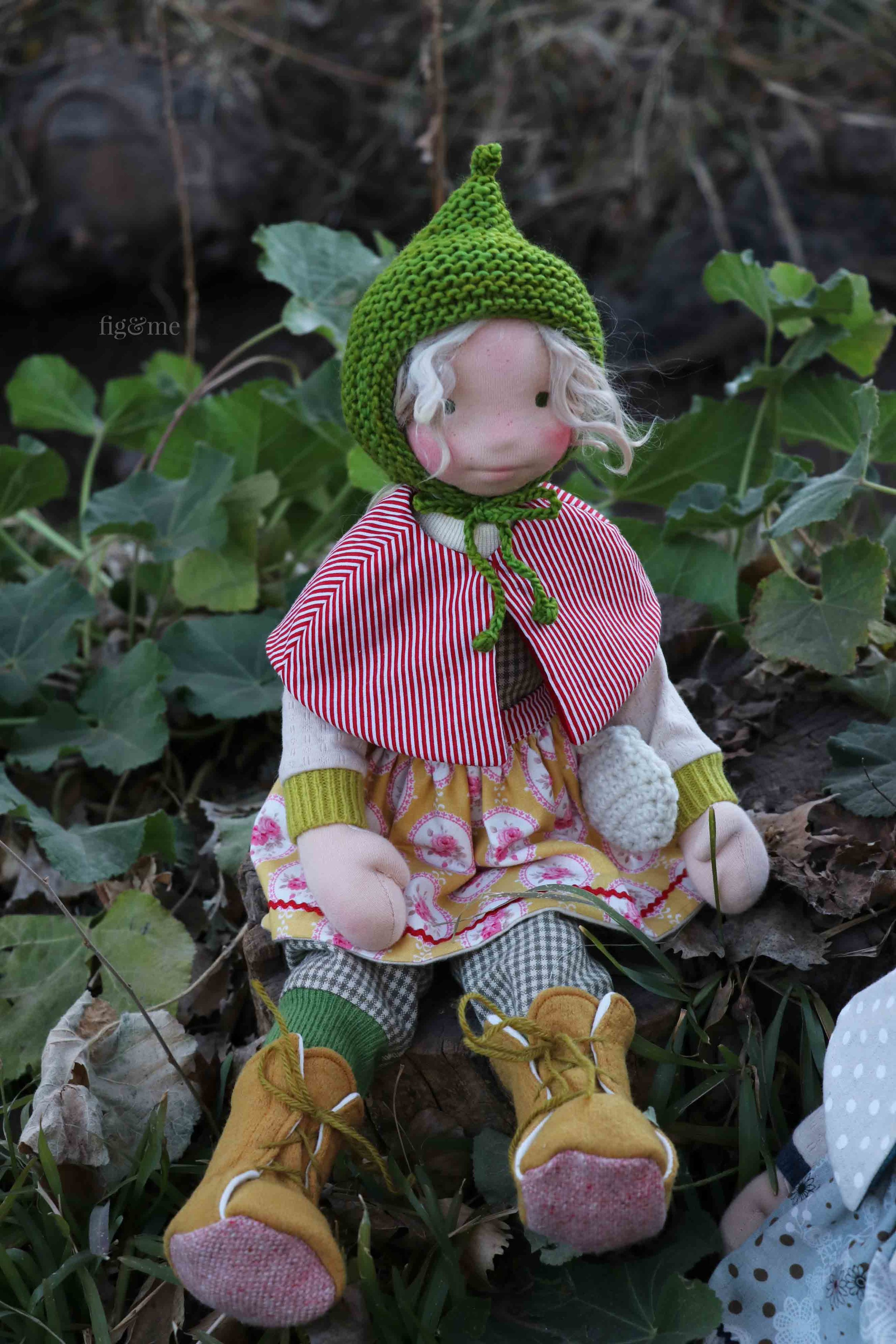 Snow White in her gardening outfit: soft cotton overalls, long wool boots, floral apron, red-stripe cape and hand-dyed-wool knitted bonnet. by Fig and Me.