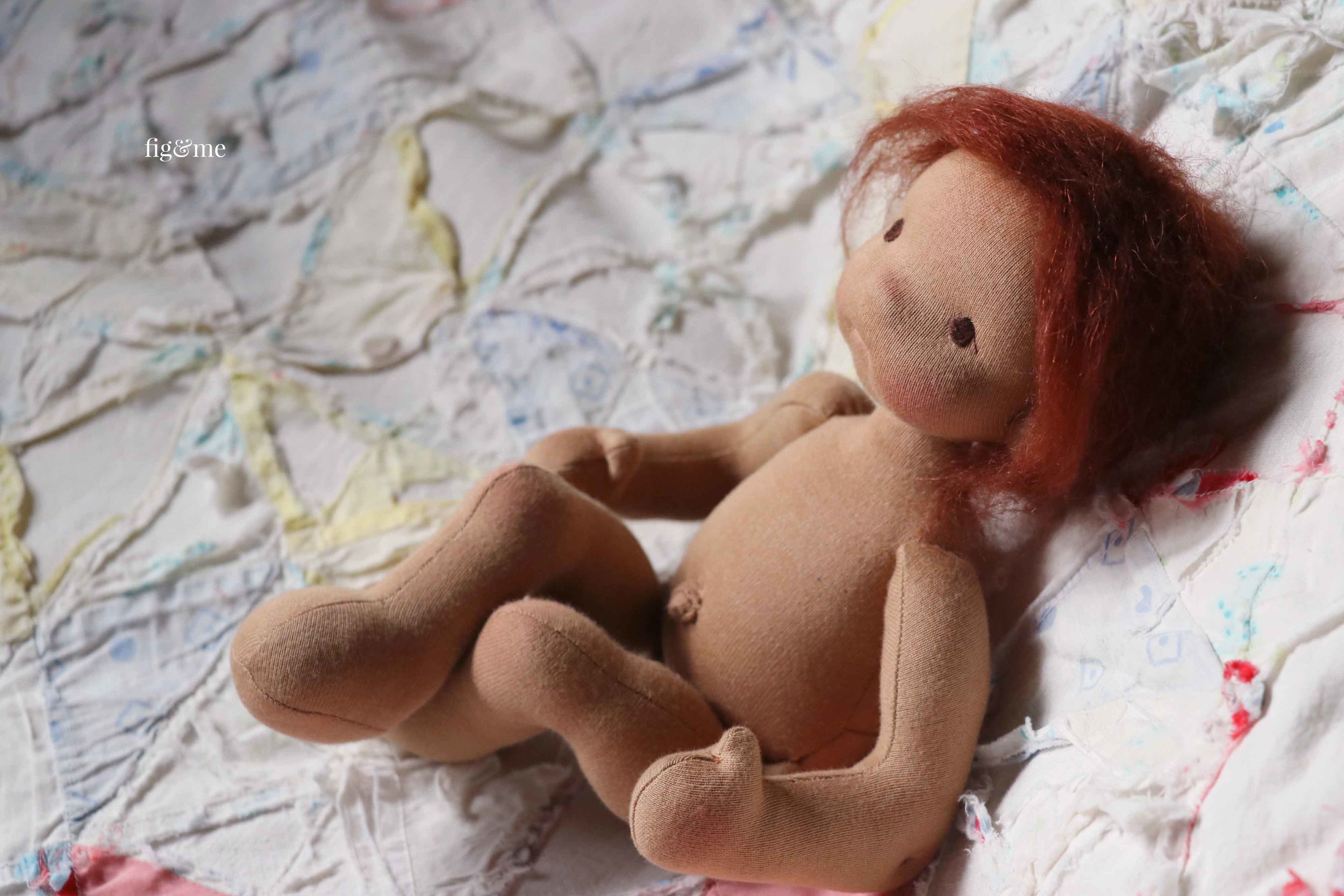 Learn dollmaking with the Baby Fig doll pattern, which introduces you to needle-felting techniques for face construction, mohair wig making, and using wool to stuff your doll. Pattern by Fig and Me.