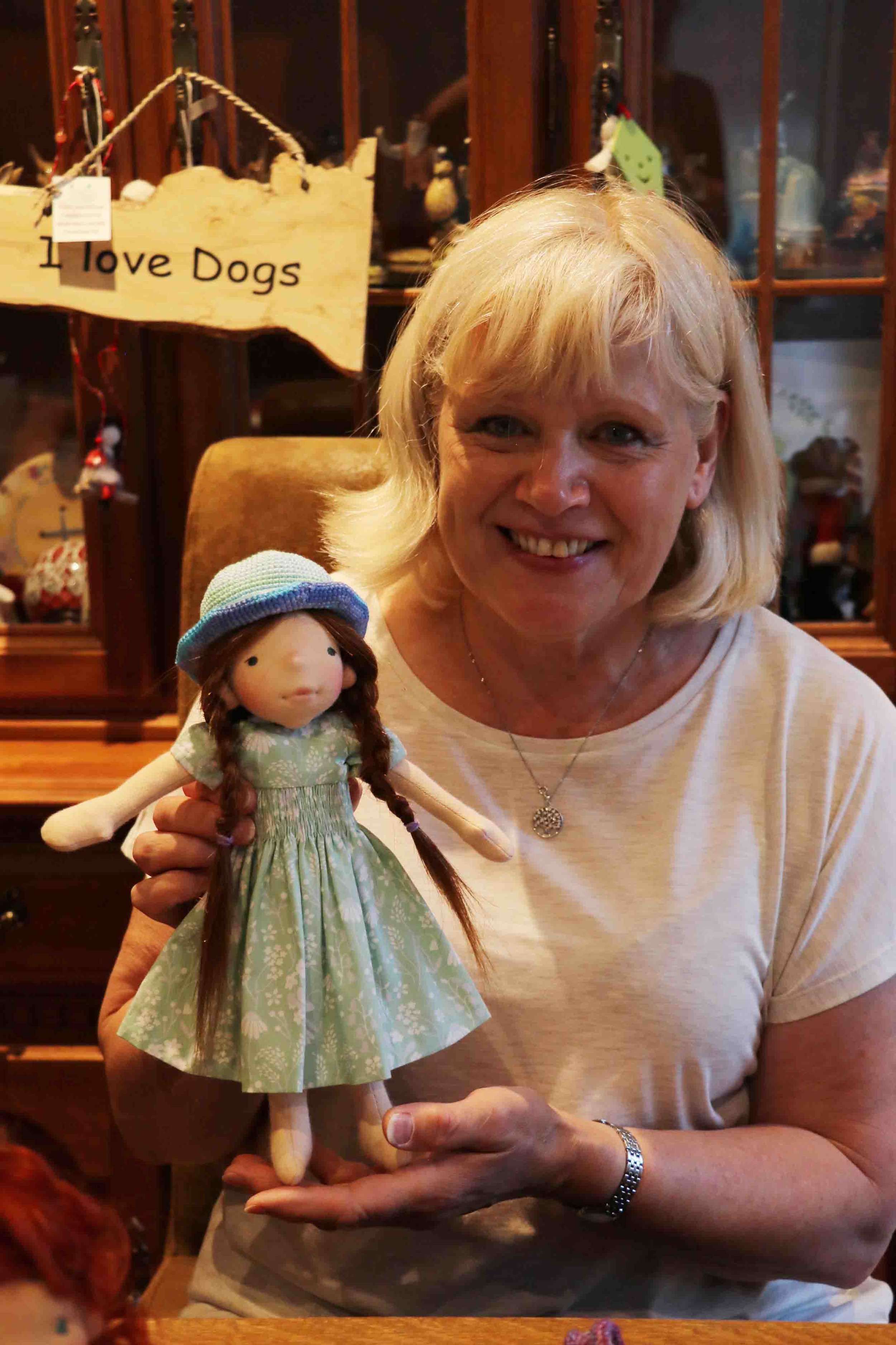 Ultra creative Gina holding her beautiful doll, and look the beautiful clothes she made for her. Fig and me doll workshop.