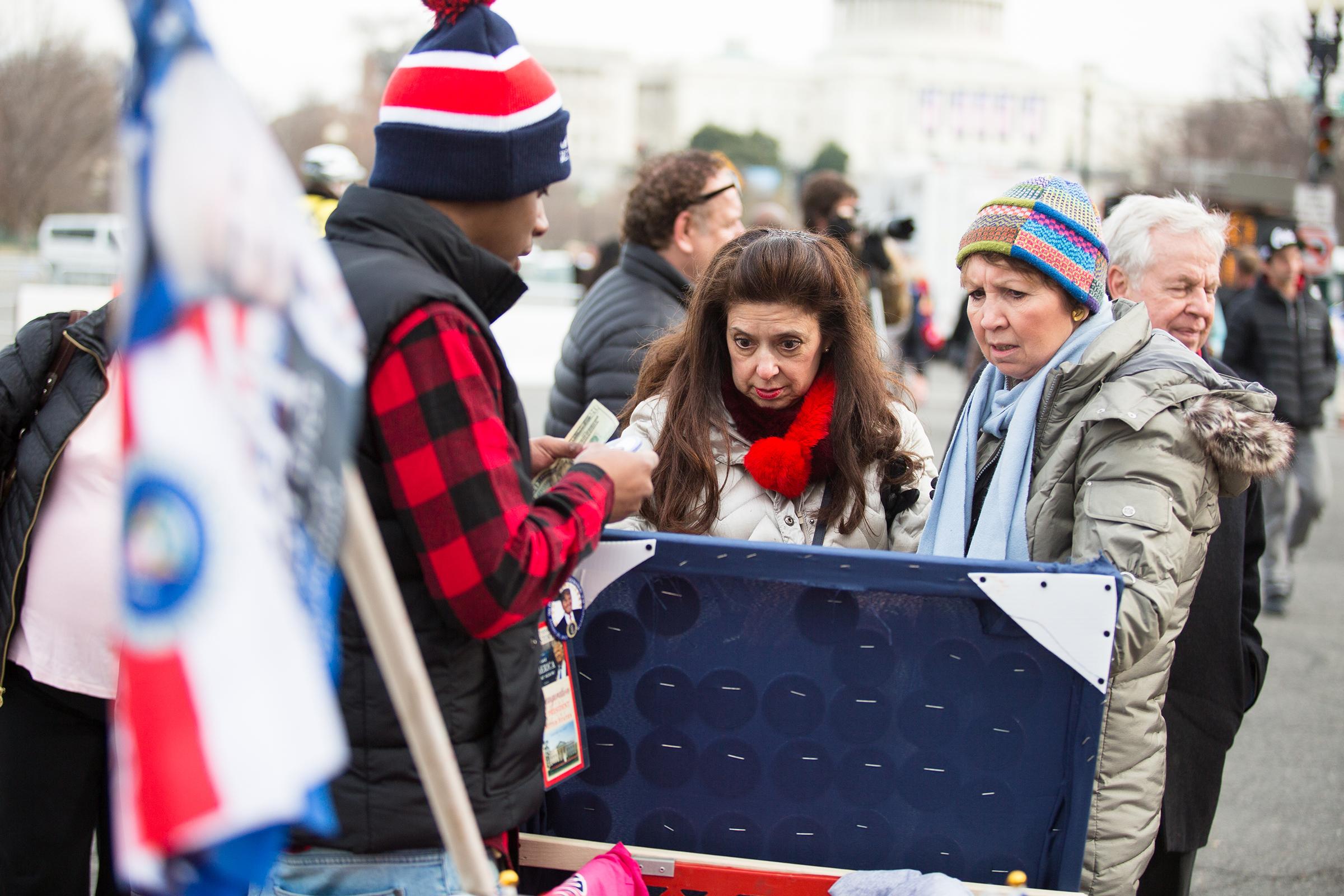 Two women buy Trump merchandise from Tim Moore along Pennsylvania Avenue on Jan. 19, 2017.