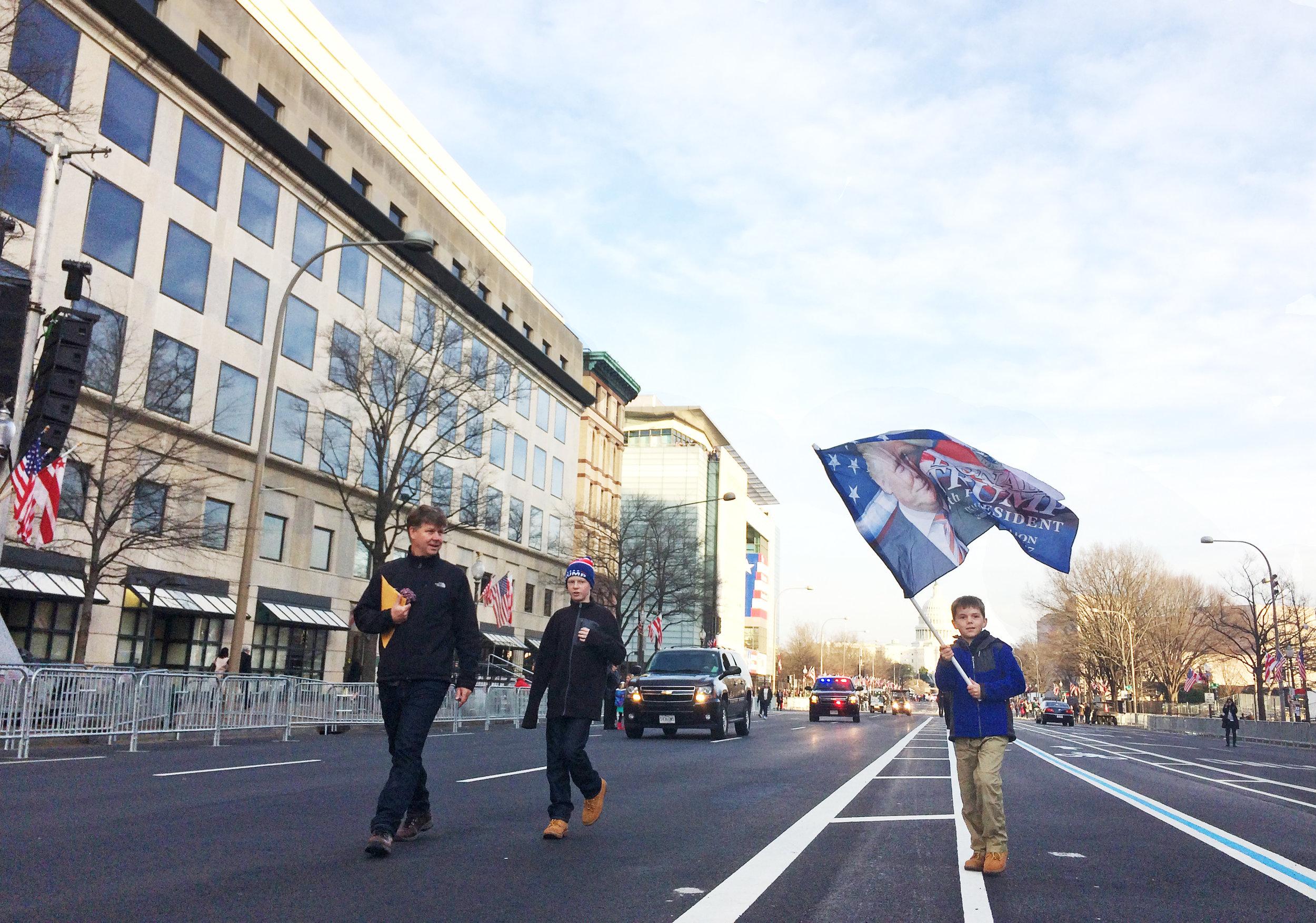 A boy walked down Pennsylvania Avenue in Washington D.C., waving a flag picturing Donald Trump, on Jan. 19, 2017.