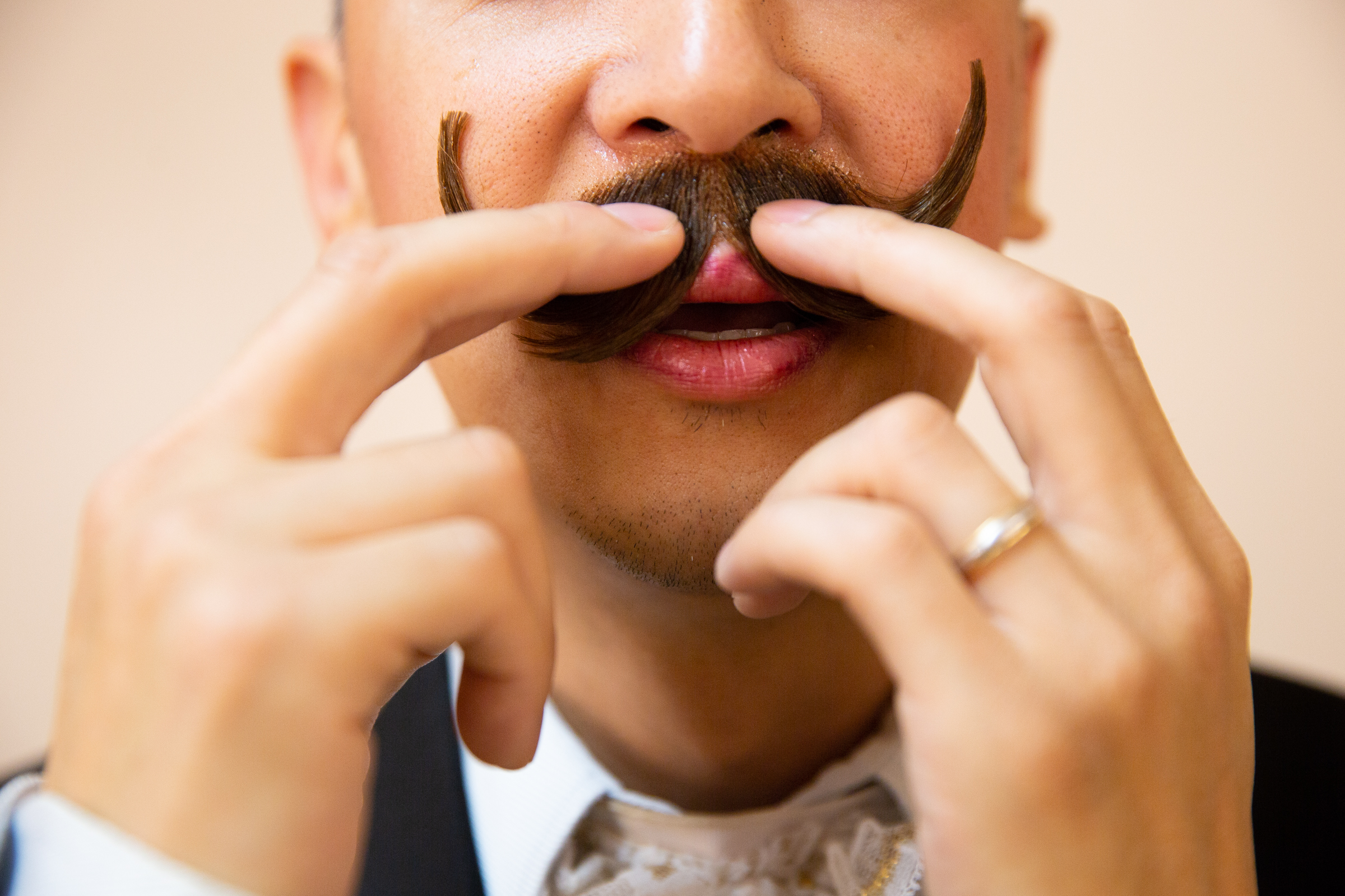 """Ernest Hui holds his fake mustache in place while it dries backstage in the men's dressing room for Western Ballet's production of """"The Nutcracker"""" at the Mountain View Center for the Performing Arts on Dec. 2, 2018."""