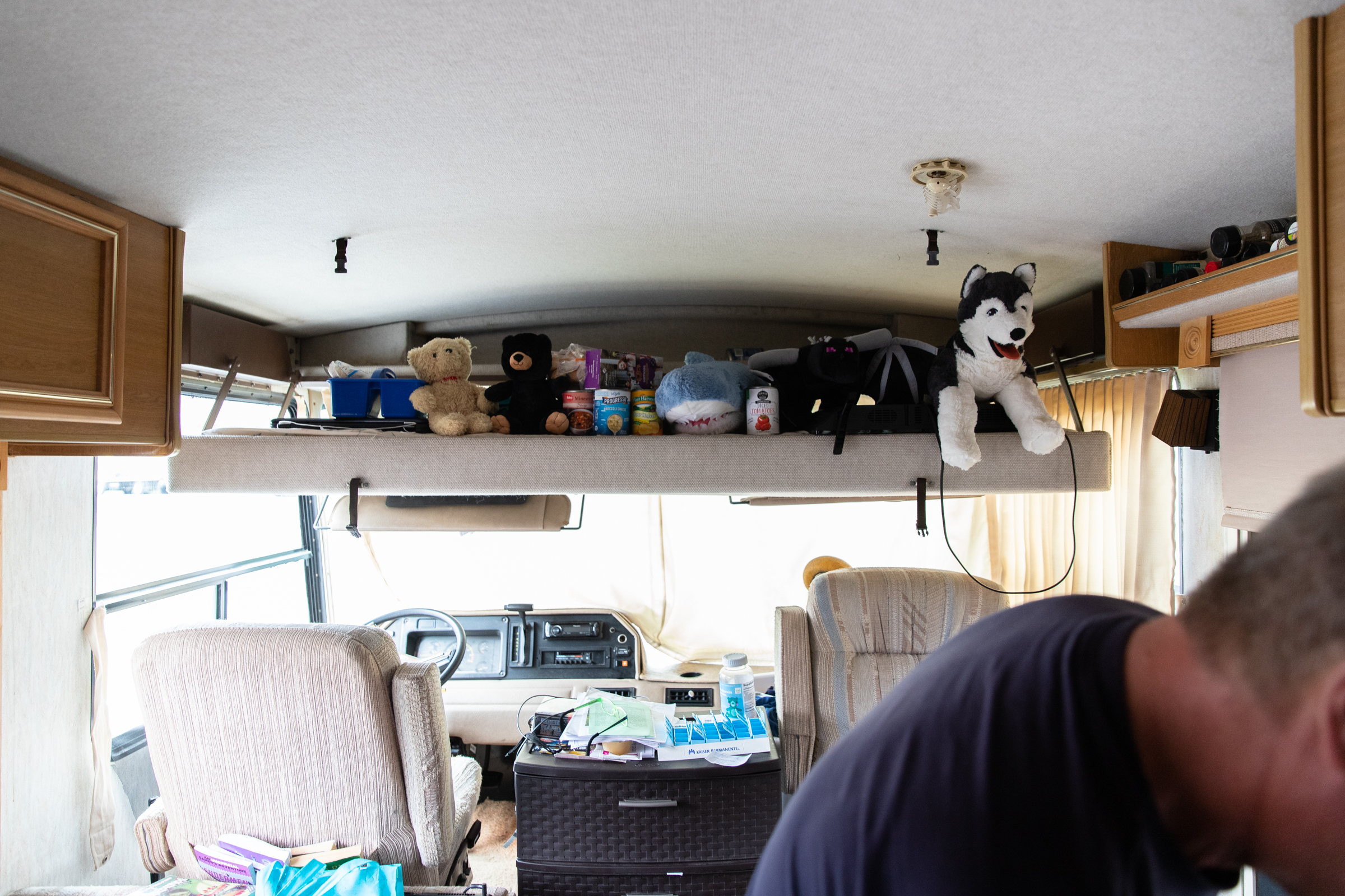 The space above the driver's seat serves as a makeshift pantry and storage area in Scott Rodvold's motorhome.  Every 72 hours, loose belongings must get strapped down so he can move the vehicle.