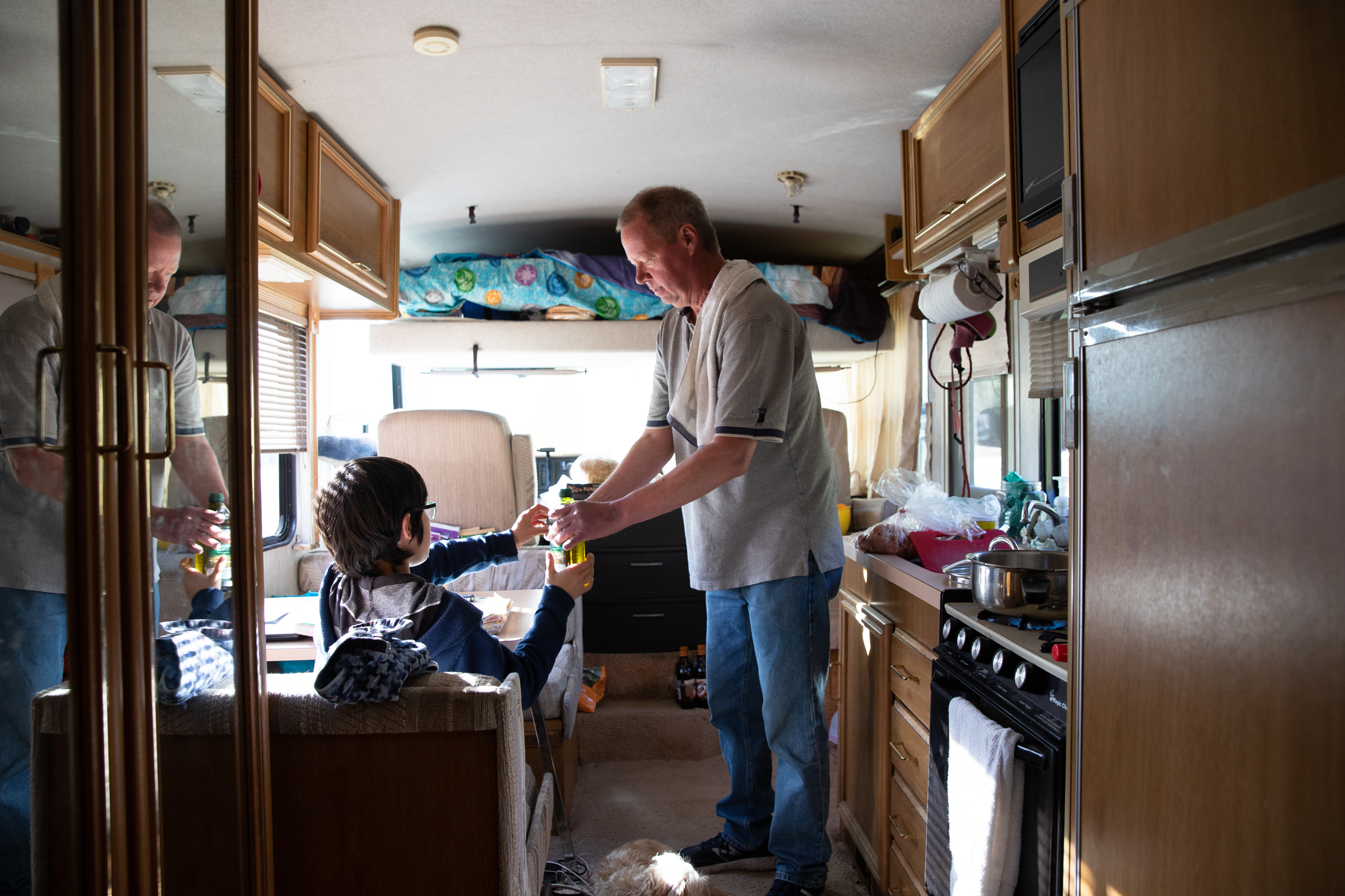 Scott Rodvold takes a bottle of olive oil from his son while preparing dinner in the motorhome they share on March 8. Depleted finances following a medical emergency made it impossible to stay in his Mountain View apartment, he said.