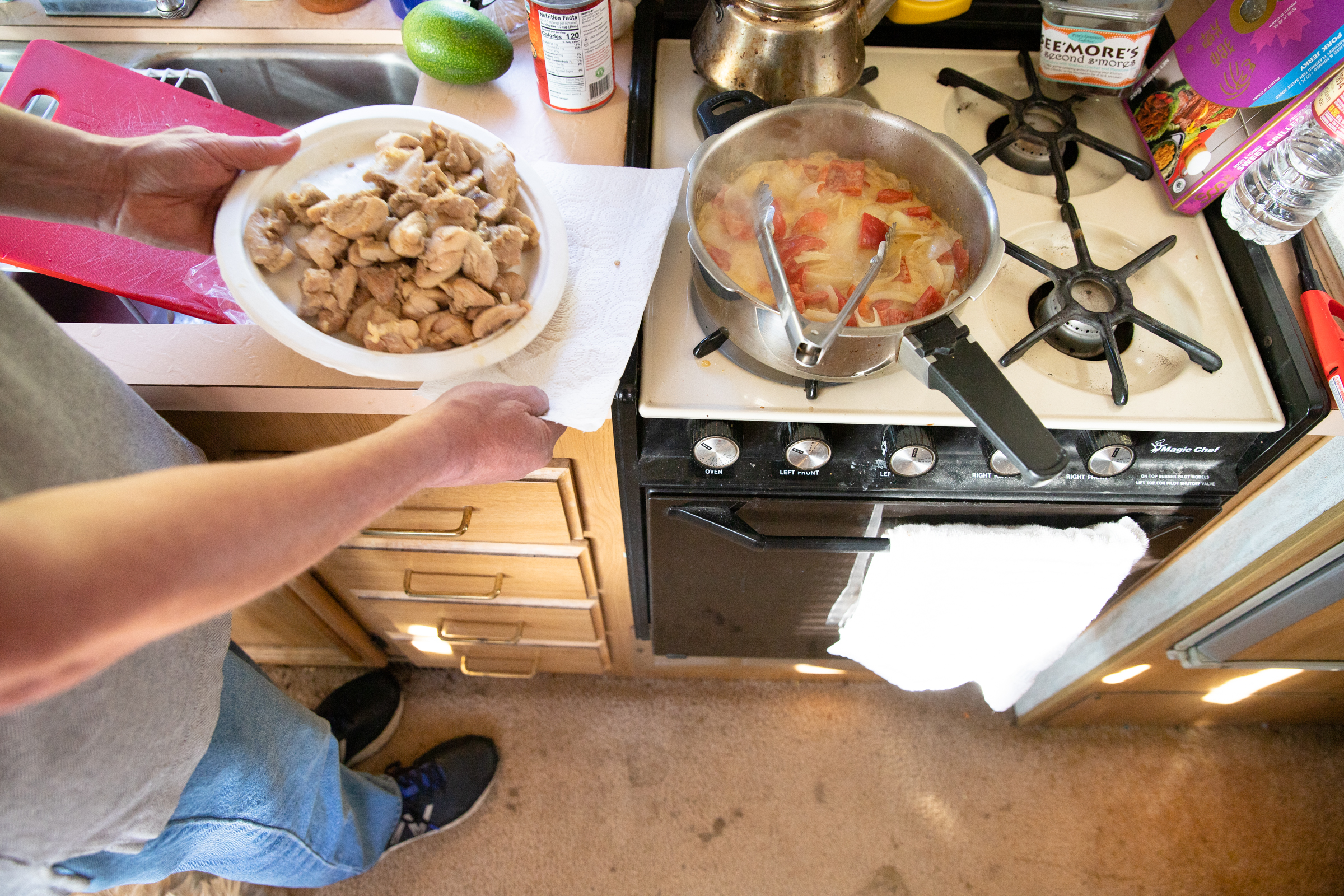 Scott Rodvold cooks Thai curry with chicken for dinner in his motorhome's kitchen on the evening of March 8.