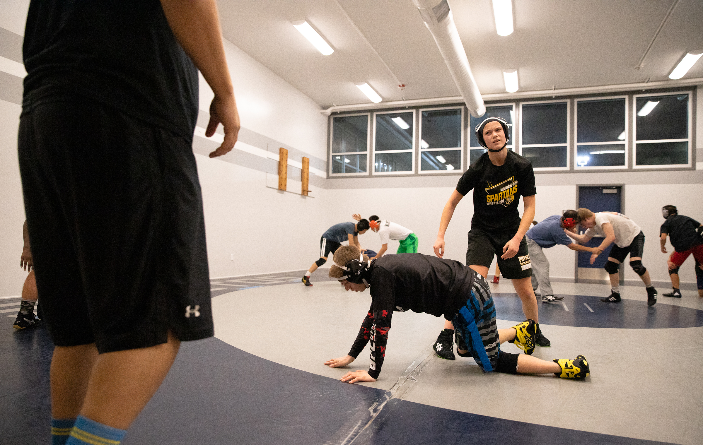 Mountain View High School sophomore Paris Harrell takes a break from wrestling Adan Scafidi, a freshman at MVHS, in the Los Altos High School wrestling room in Los Altos, California, on Jan. 30. The two athletes are in the same weight class and can practice against one another.