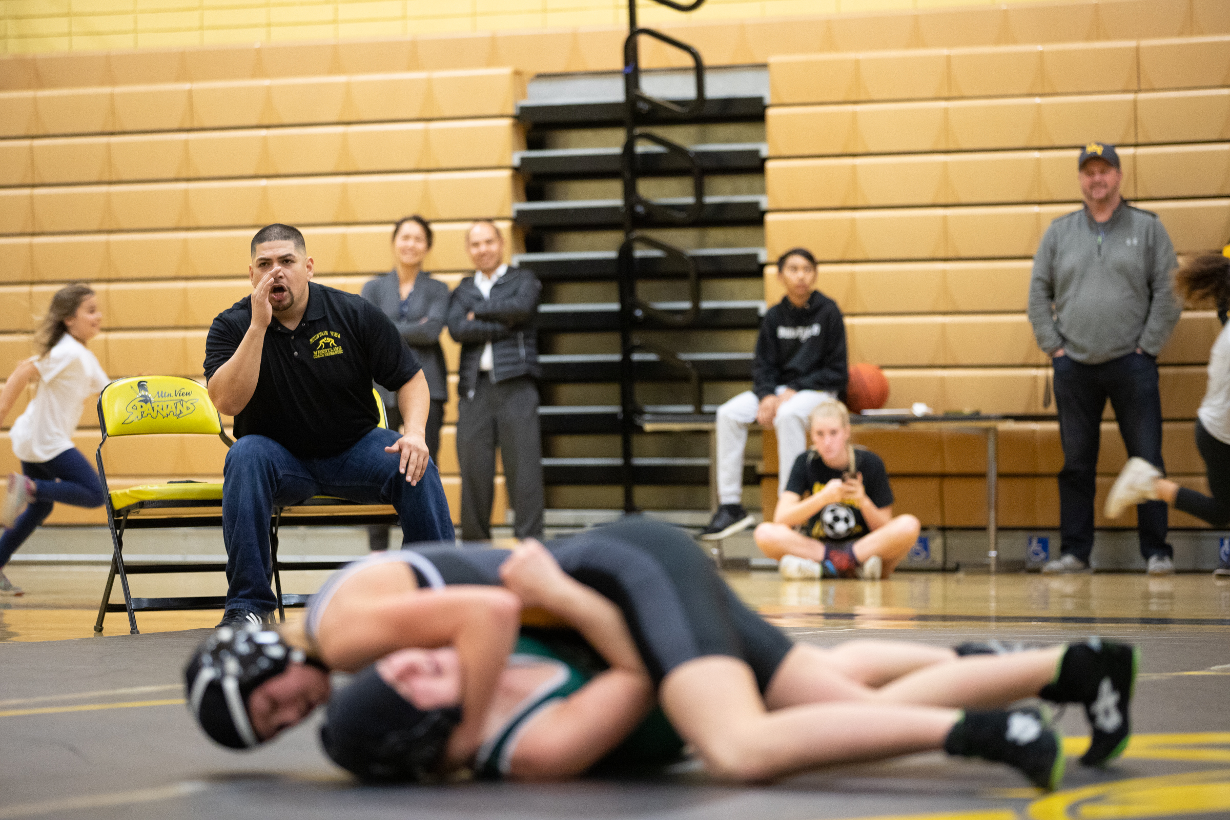 Francisco Hernandez, Mountain View High School's wrestling coach, encourages Paris Harrell during a fight against Ava Aufderheide, a student from Homestead High School, during a home meet in Mountain View, California, on Jan. 31. Seconds later, Harrell pinned Aufderheide and won her first fight of the season.
