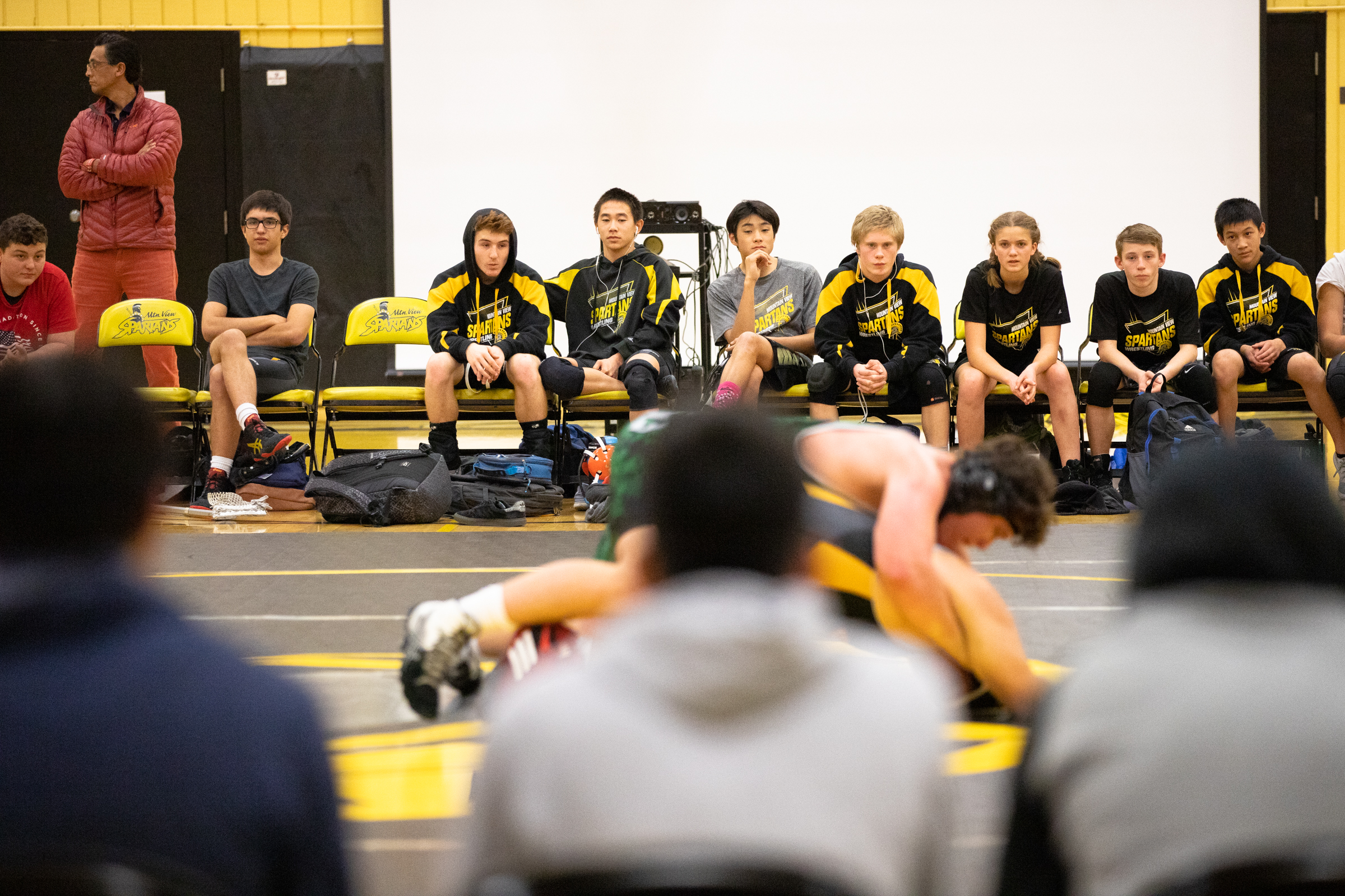 Paris Harrell, 15, is the only female member of Mountain View High School's wrestling team. She sits with her teammates watching a fight against Homestead High School at a home meet in Mountain View, California, on Jan. 31.