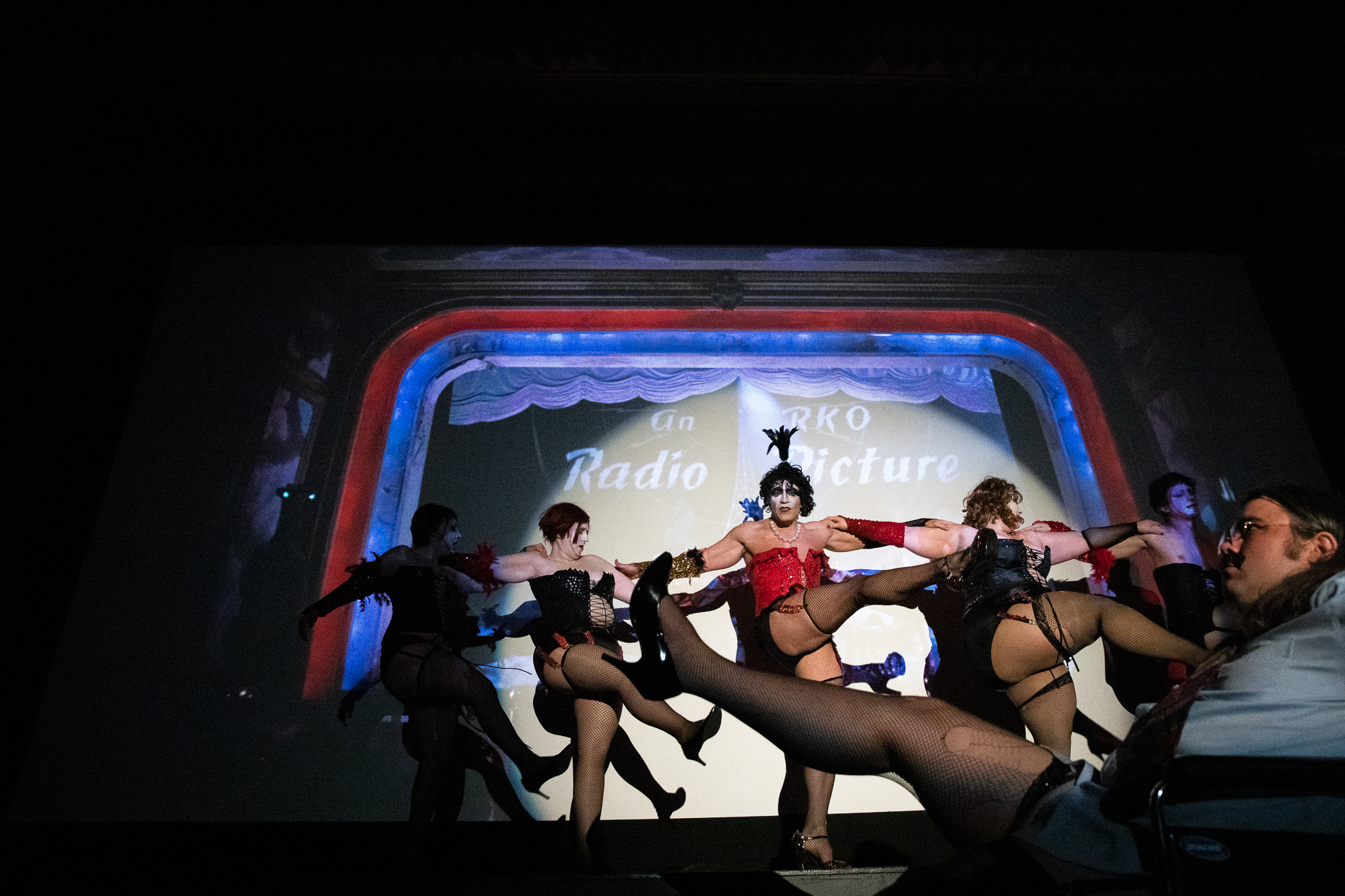 "The Bawdy Caste actors perform the cabaret scene in front of the projected film during a midnight showing of ""The Rocky Horror Picture Show"" at the Guild Theatre on April 6."