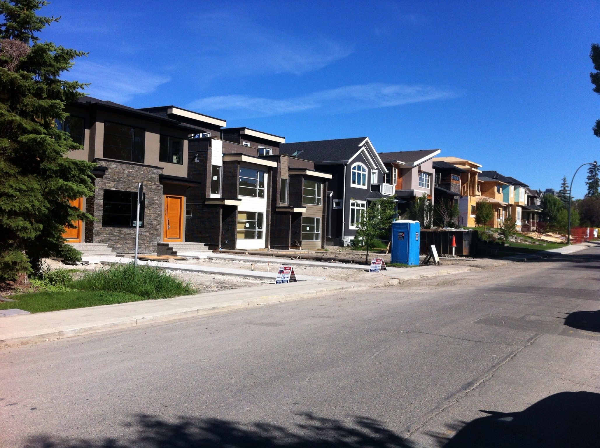 I had to take a second look when I turned on to this Hillhurst street in Calgary's thriving city centre.  At first glance you would think it is a parade of show homes in a new suburb 20+km from downtown. But no this is just one of many streets with multiple infill homes being built within 5 km of dowtown.