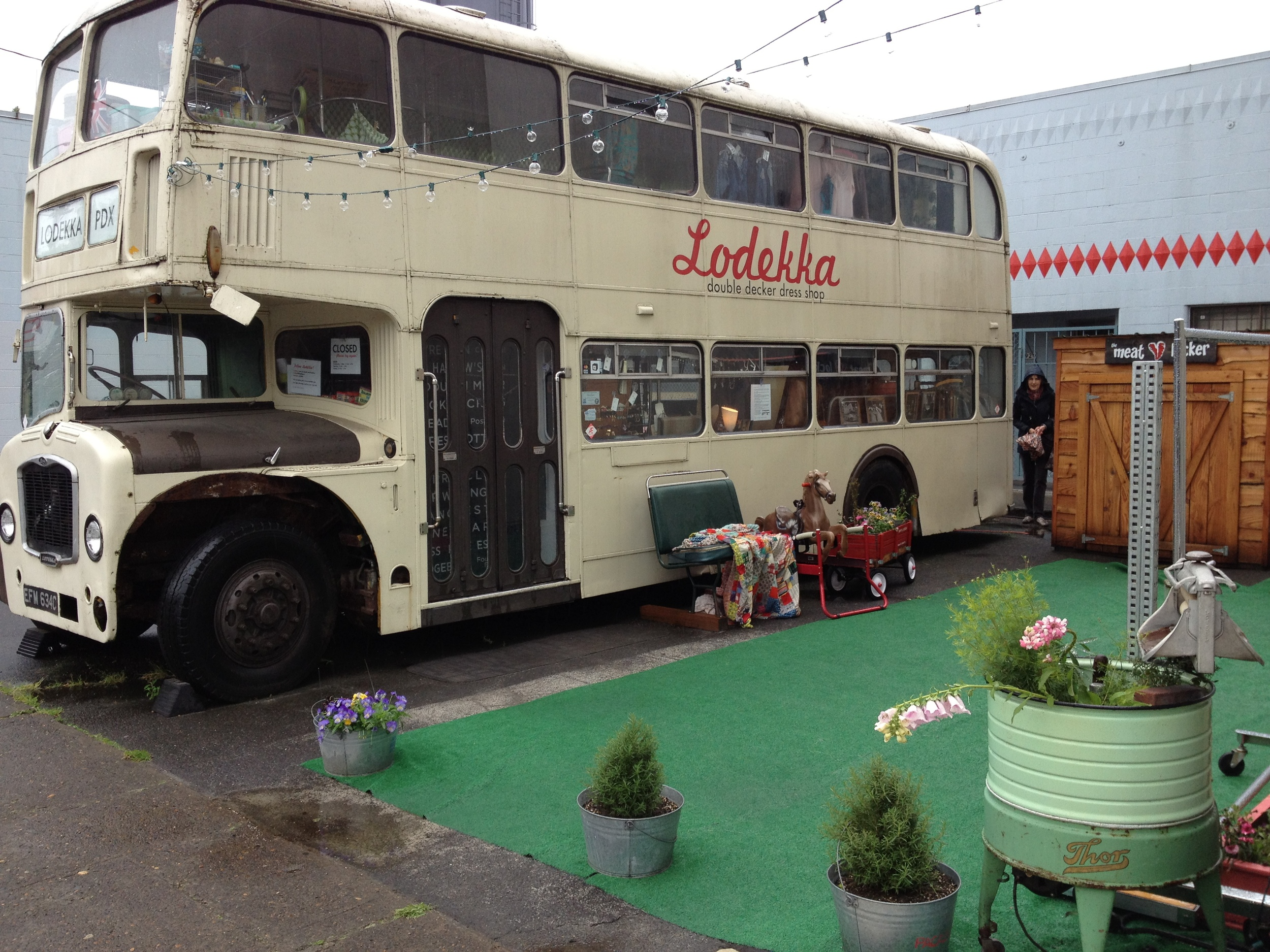 "The Lodekka bus is parked on a plaza on North Williams Ave. complete with its own garden outdoor living room.  Inside it is packed with vintage clothing.  It doesn't get much more bohemian that this.  The bus' nickname is ""Ginny"" and she operated in Liverpool from 1965 to 1982."