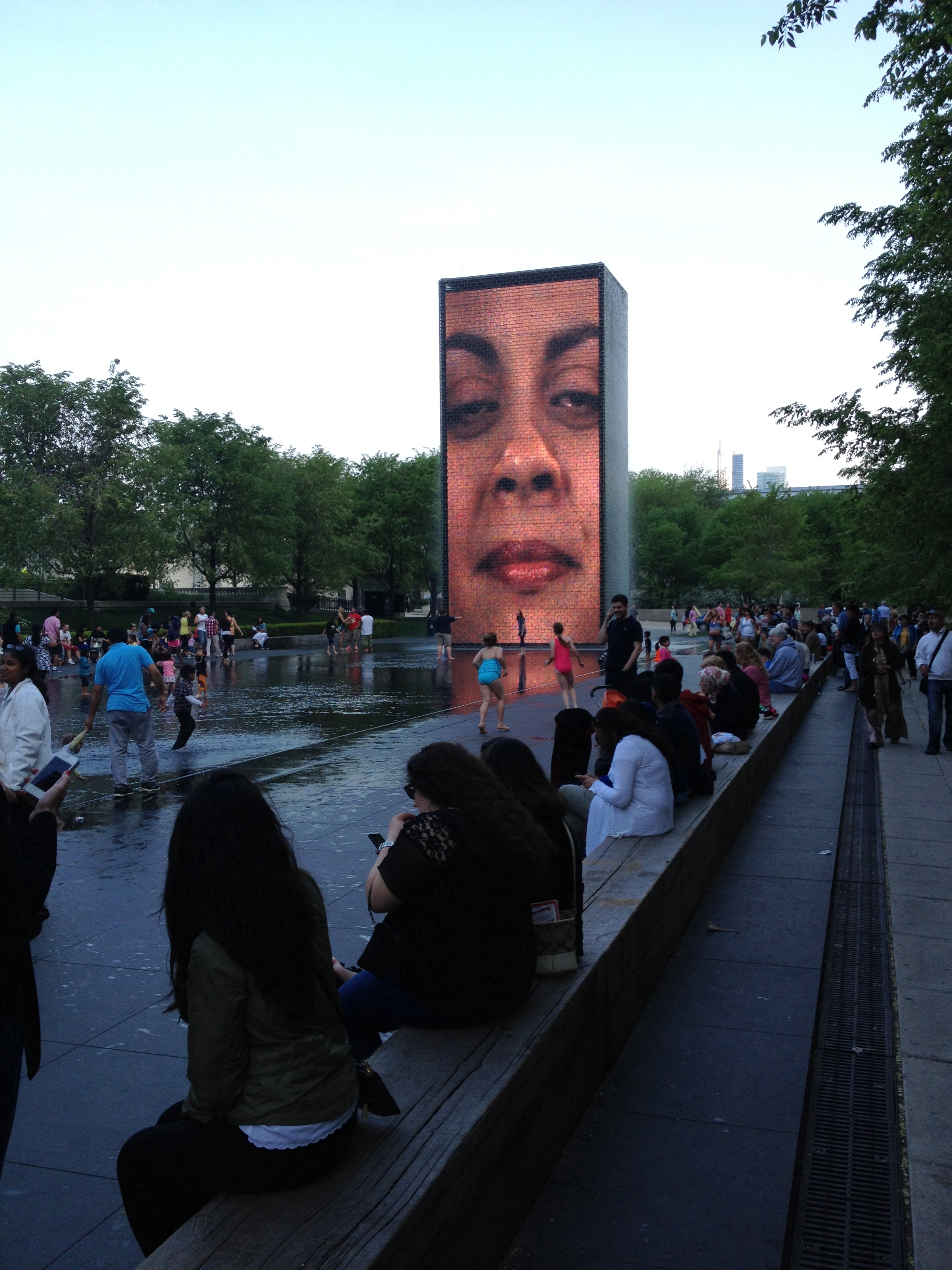 Plensa's Crown Fountain sculpture even at dusk attracts hundreds of people to interact with it.