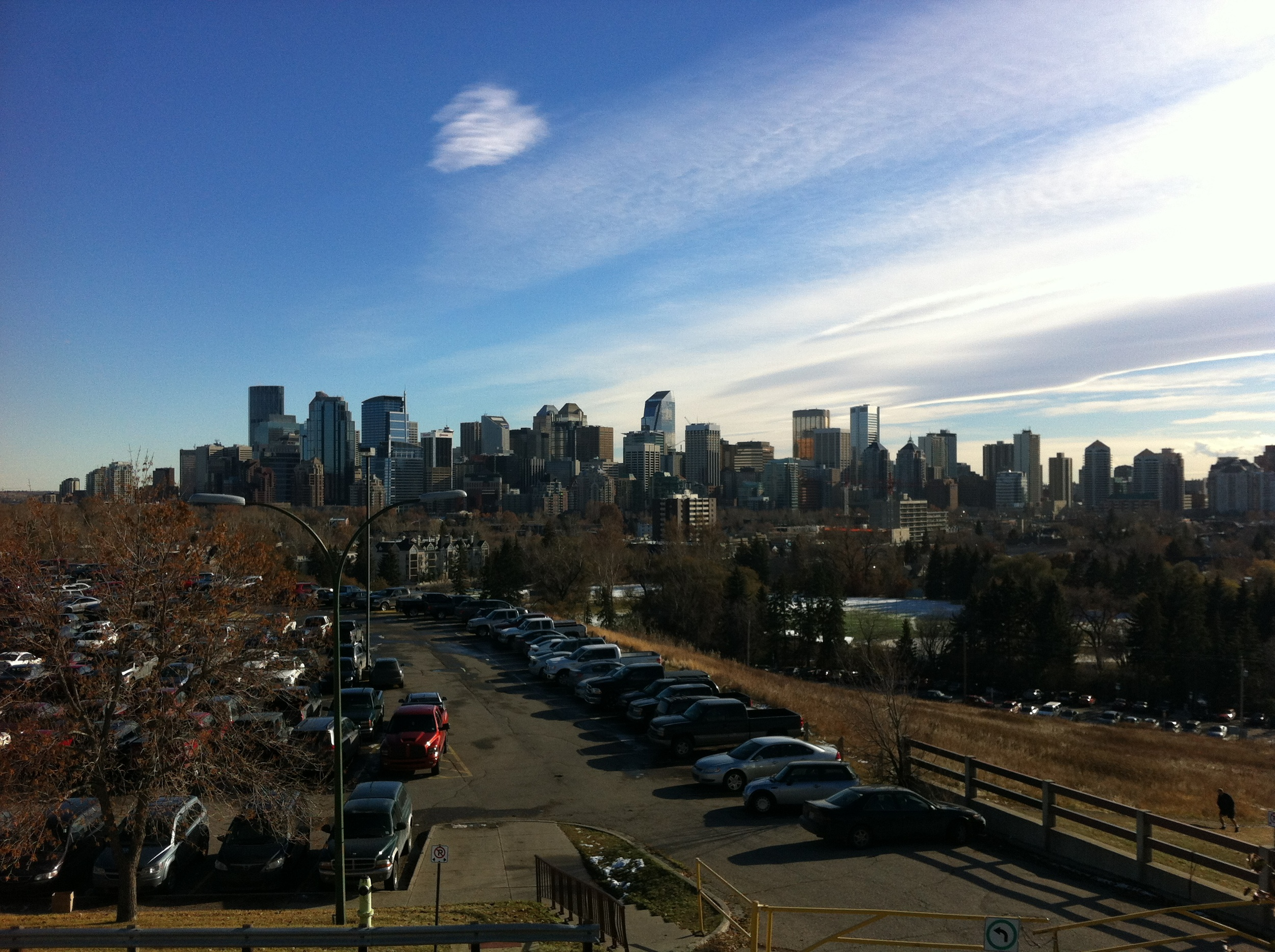 Downtown skyline from the Bow River bluff with the iconic Calgary blue sky.