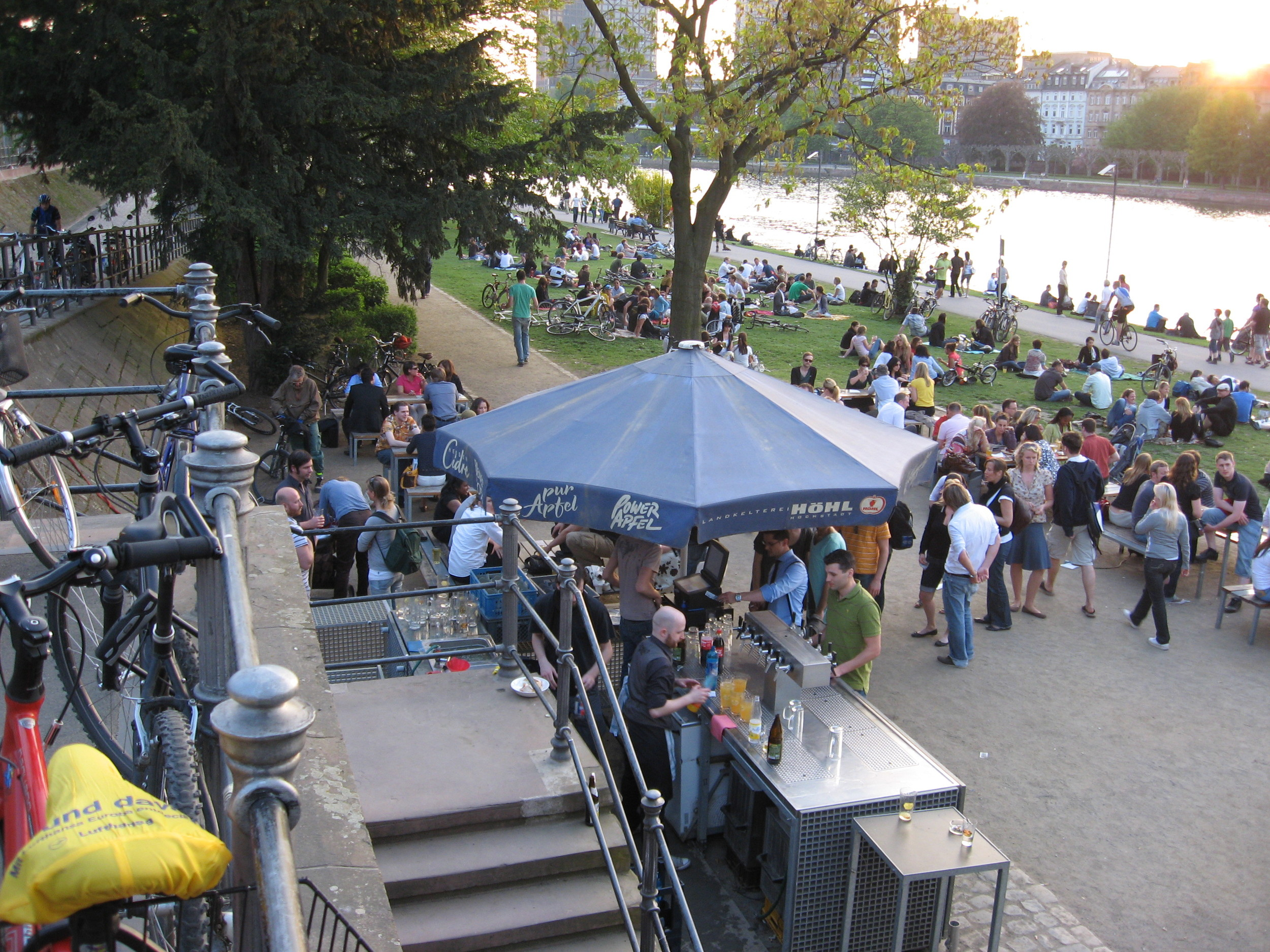 Frankfurt's green beach with beer vendor is just a narrow lawn area between the road above and the pathway along the water.