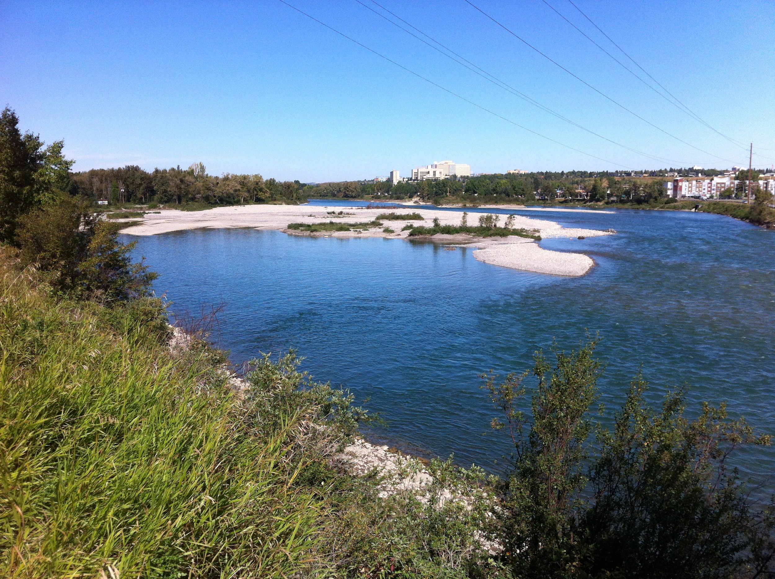 The Crowchild Trail gravel bar has the look of a white sand beach complete with its own lagoon and blue/green water.