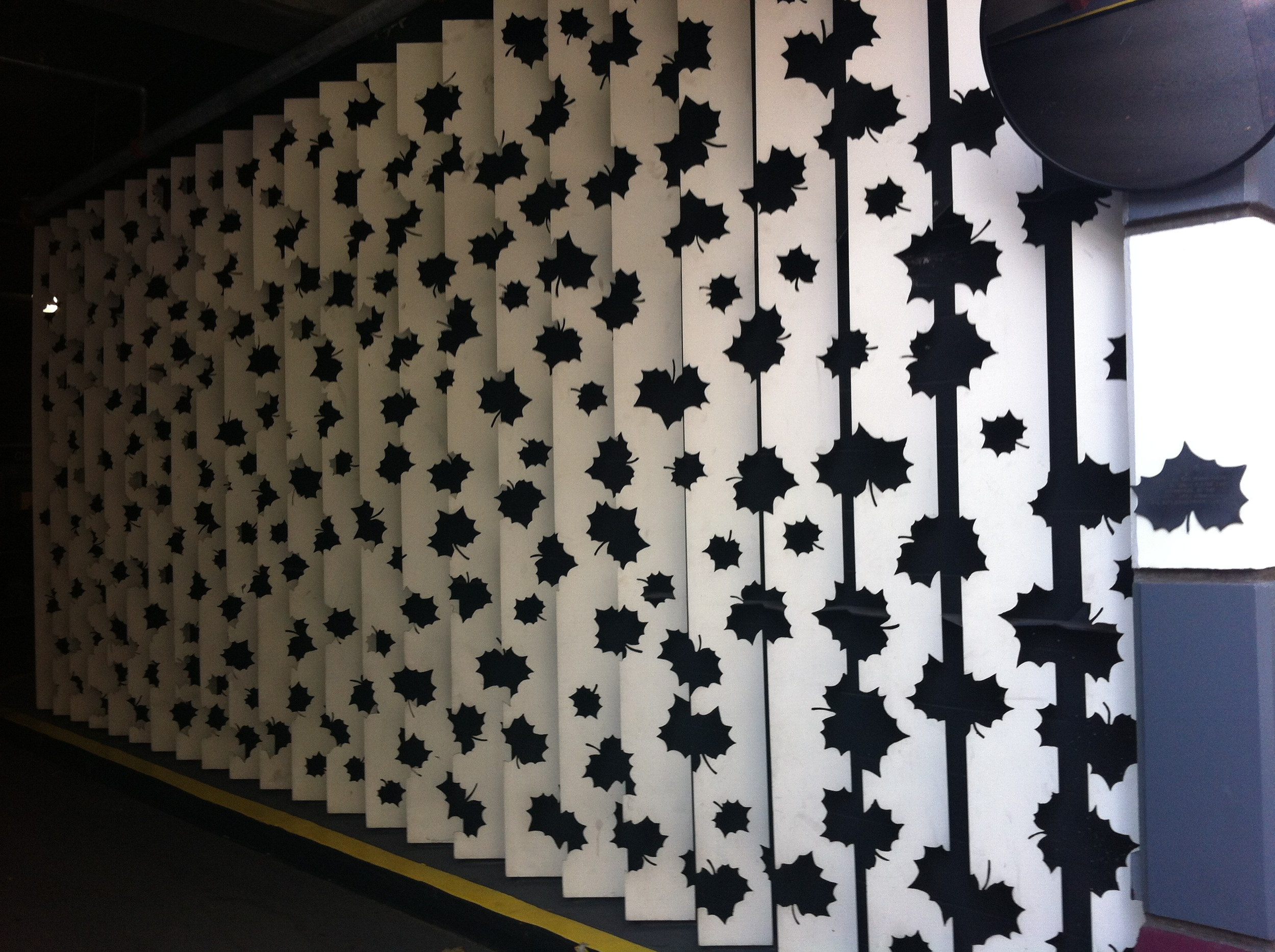 This mural Les Bois, 1992 was created by Bruce Poe and Dennis Proksa.  It consists of 24 white steel plates with a random pattern of cut leaf images against a black wall in a parking lot at street level. As you walk past the leaves evolve from whole to fragmented.