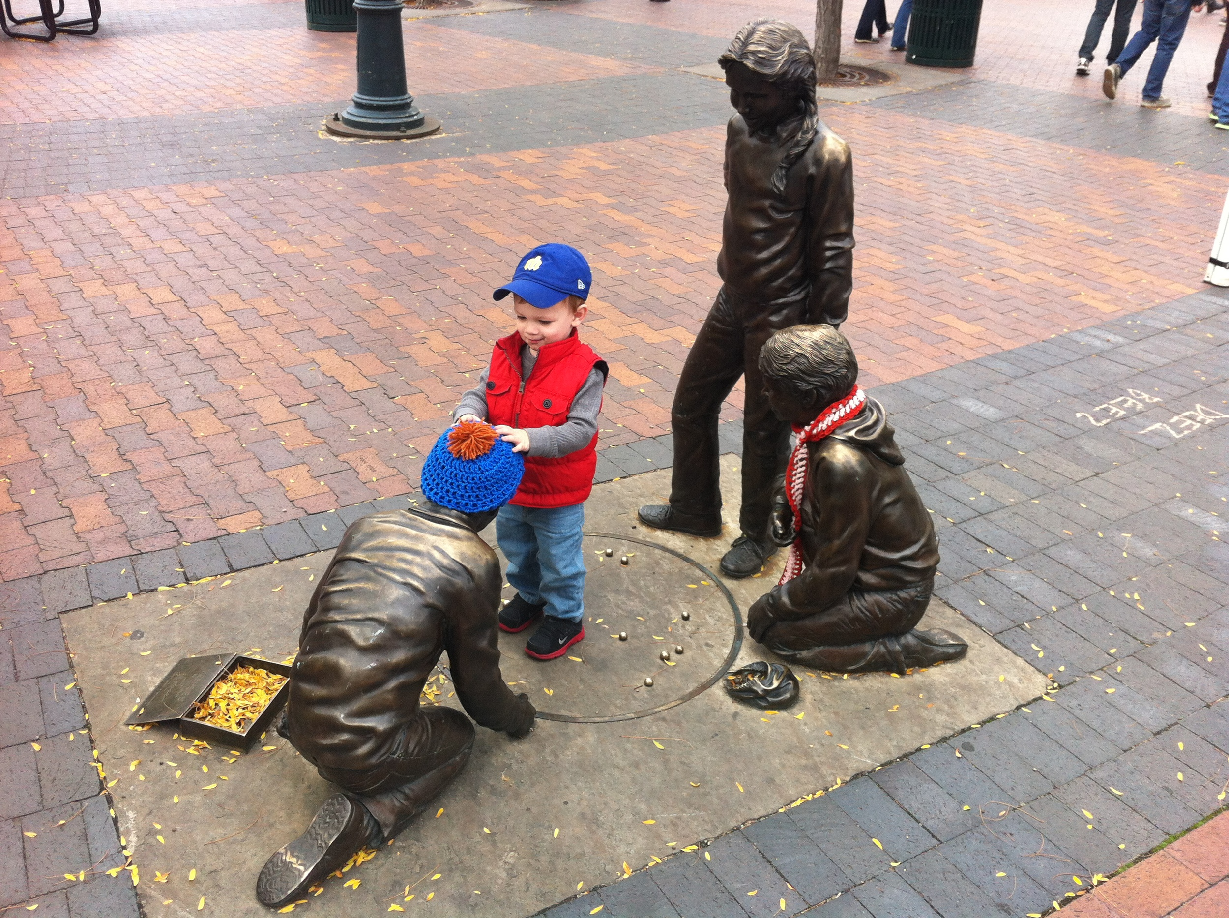 Found this little guy playing with a piece of public art depicting children playing marbles.  Urban playgrounds should appeal to people of all ages and backgrounds. It isn't just about the restaurants, shops, festivals, museums, attractions and performing arts.
