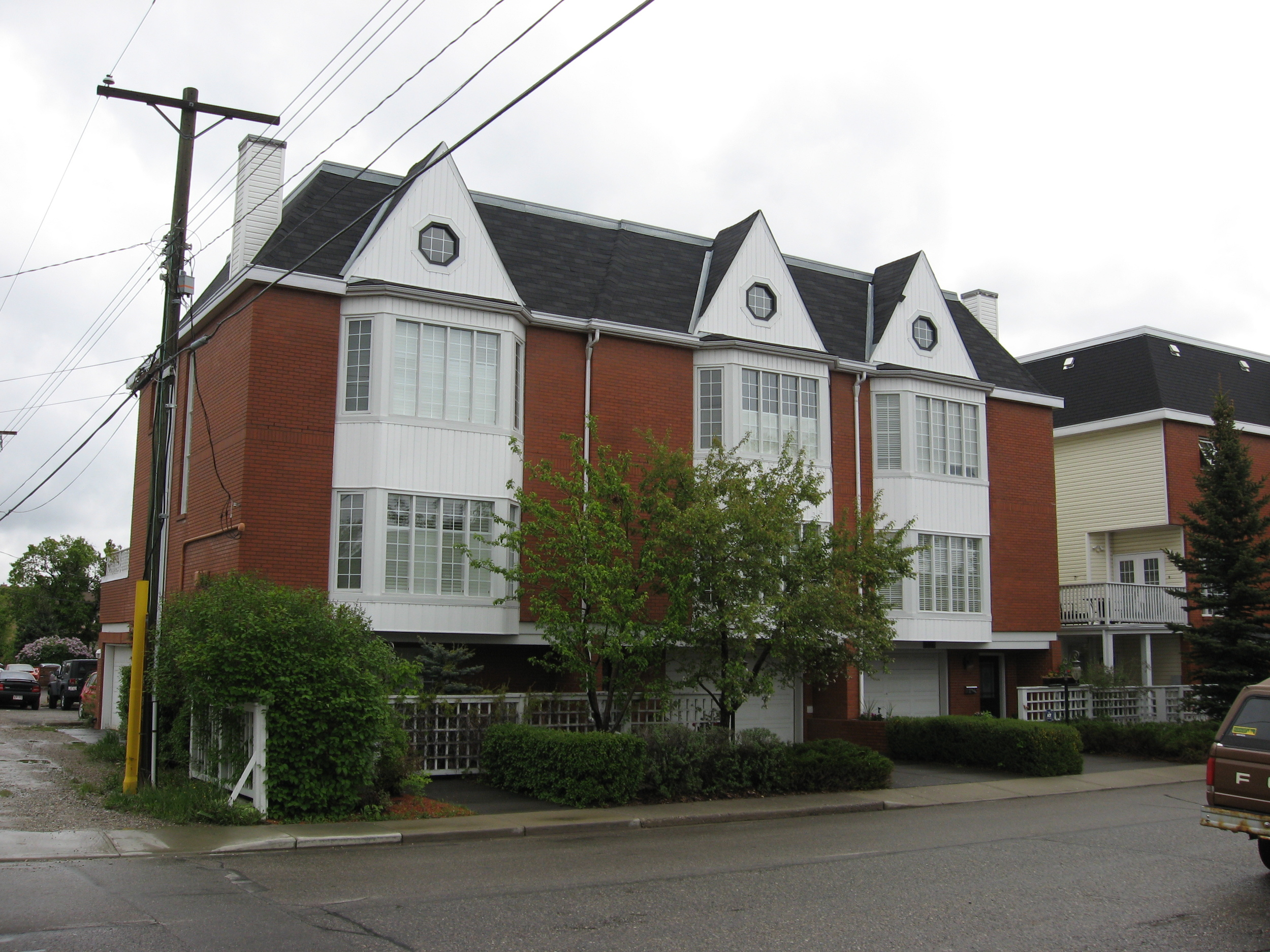 Example of infill homes with site restrictions that have been resolved with single car garages at front and garage off the alley. Facade materials are compatible with older homes in the area. The planting of small trees and shrubs also help to make these homes more attractive.