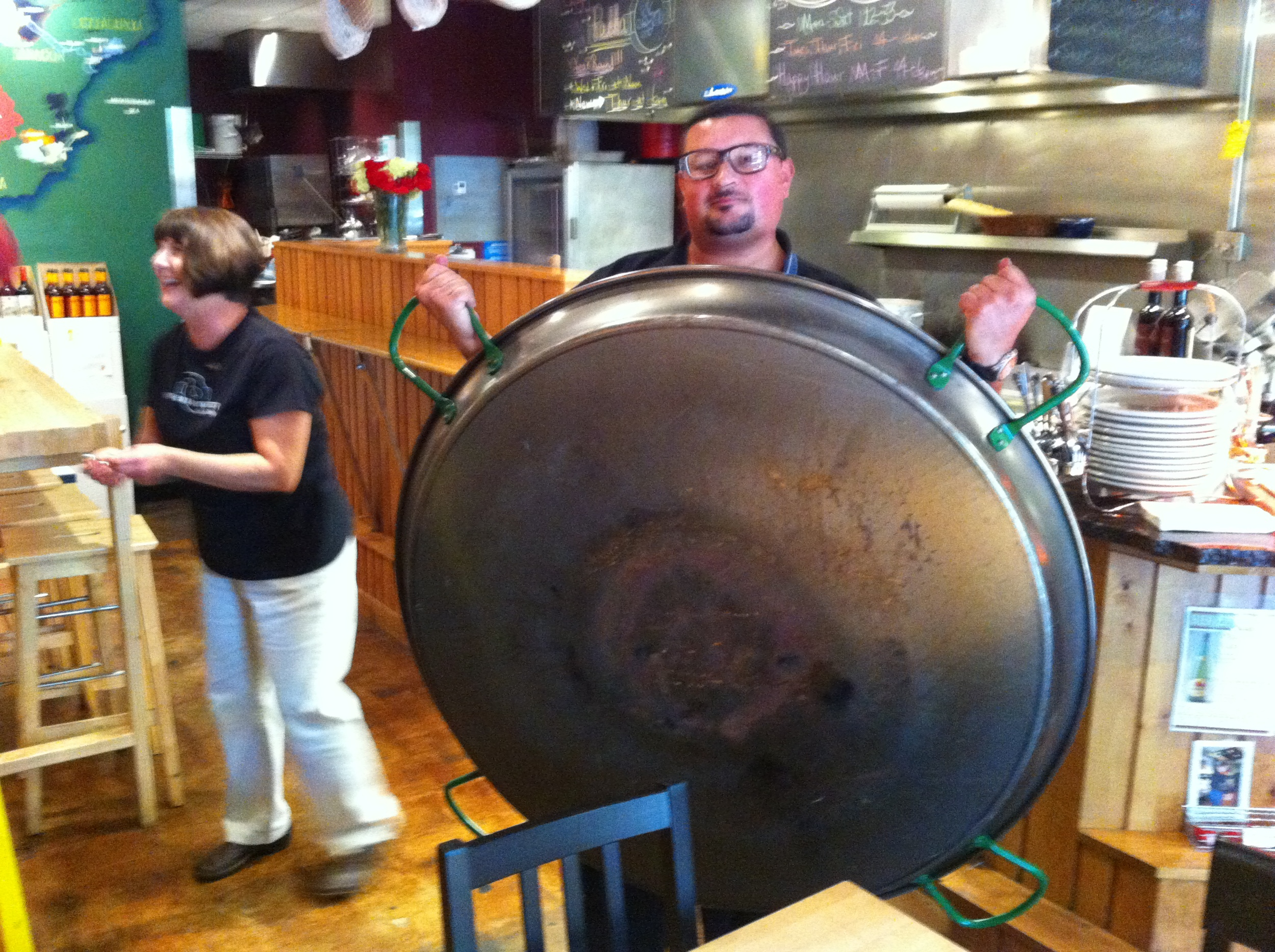 Paella pan is being removed from the ceiling to get ready for the evening feast.
