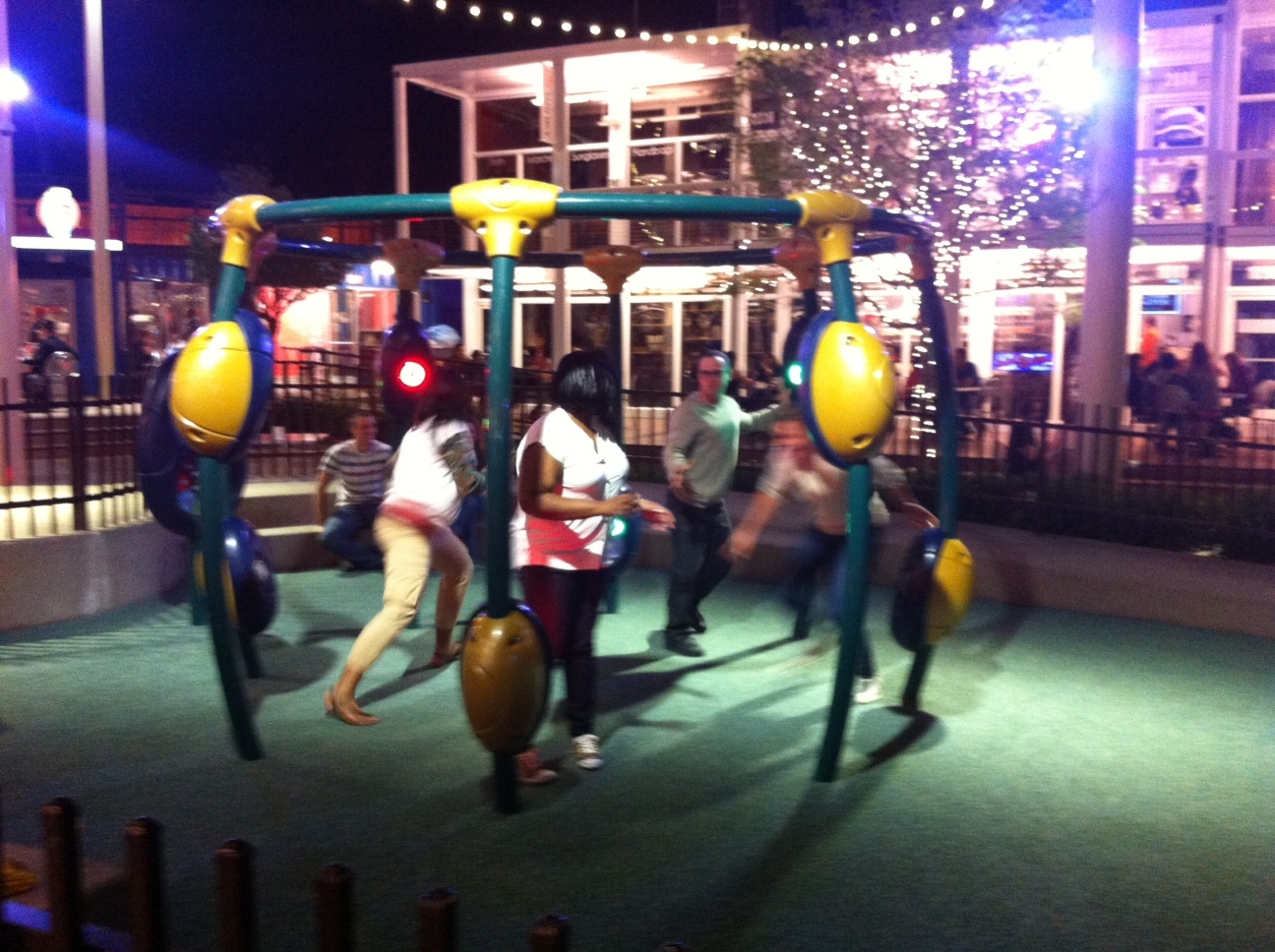 Adults enjoying the playground in Container Park at night.